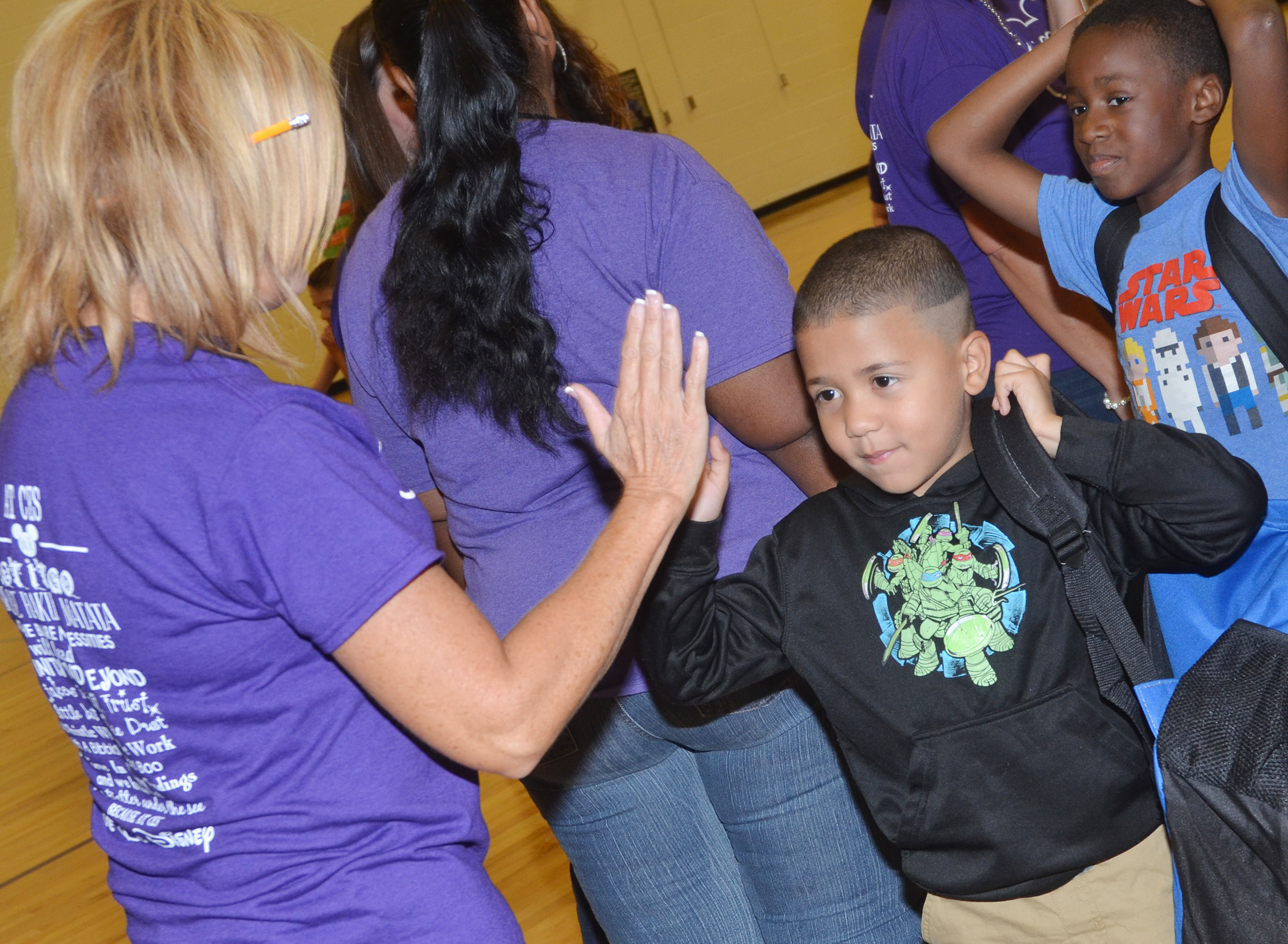 CES teacher Lisa Wiseman high-fives former student Ahryan Wilson, who is a first-grader.