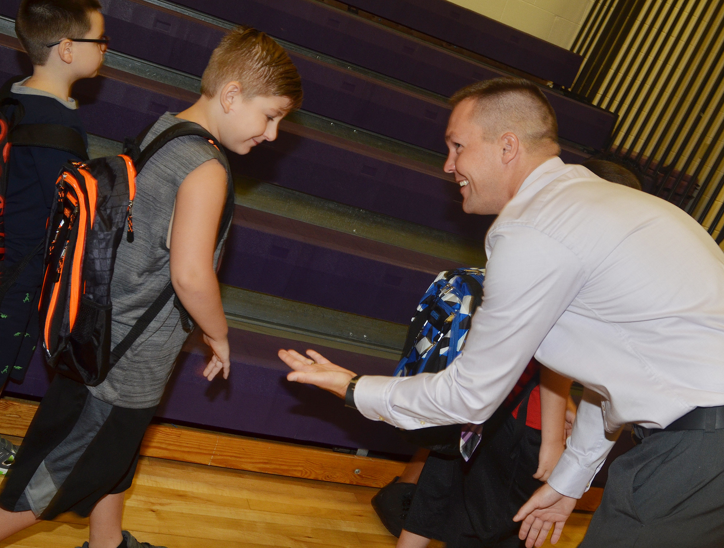 CES Assistant Principal Weston Jones high-fives third-grader Seamus Huber.