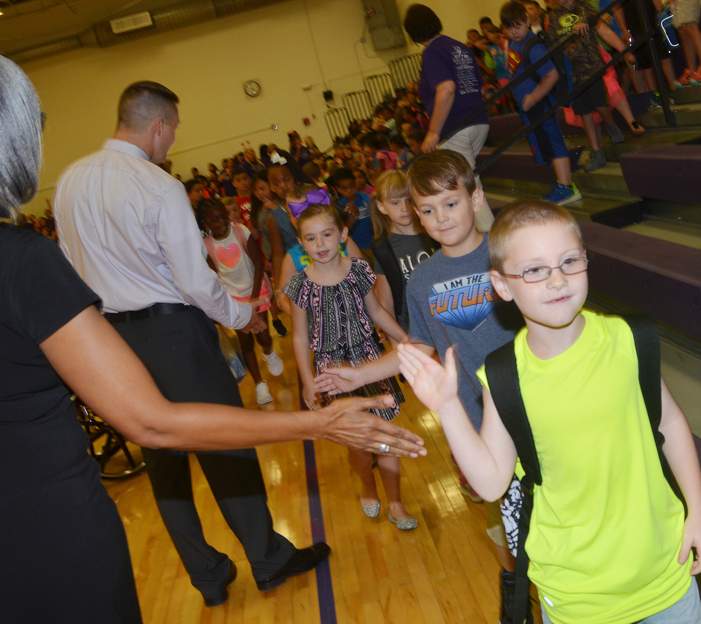 CES Assistant Principals Doretha Sanders, at left, and Weston Jones high-five James Brunner and his second-grade classmates.