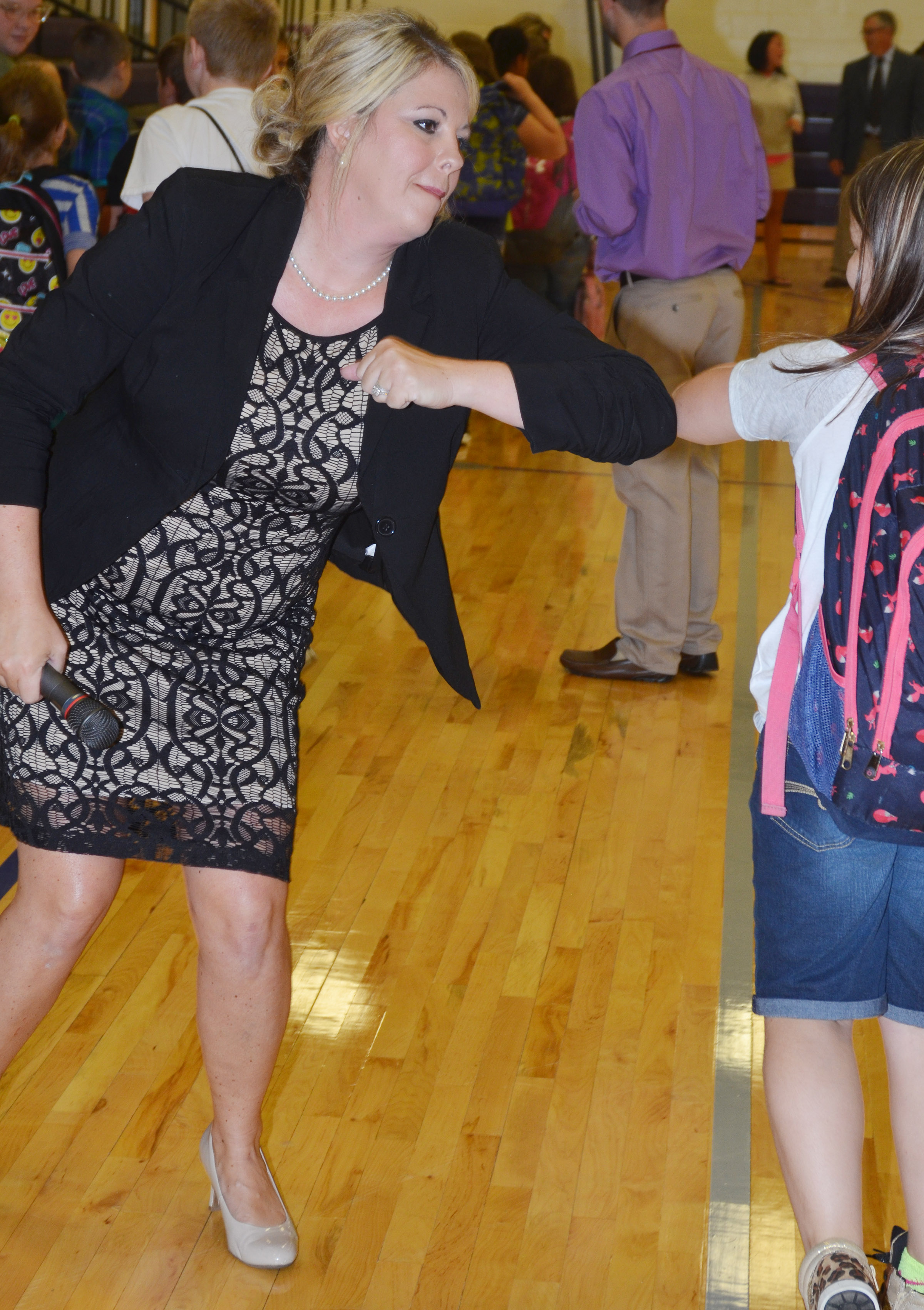 CES Principal Elisha Rhodes bumps elbows with her students.