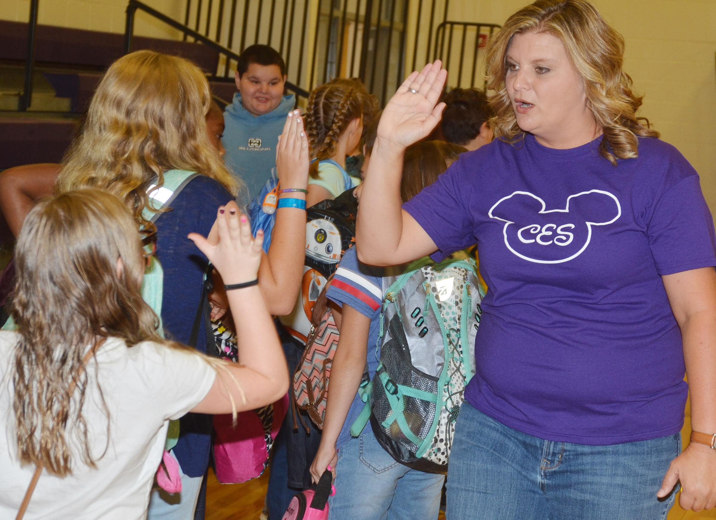 CES fifth-grade teacher Tammy Hash high-fives her students.