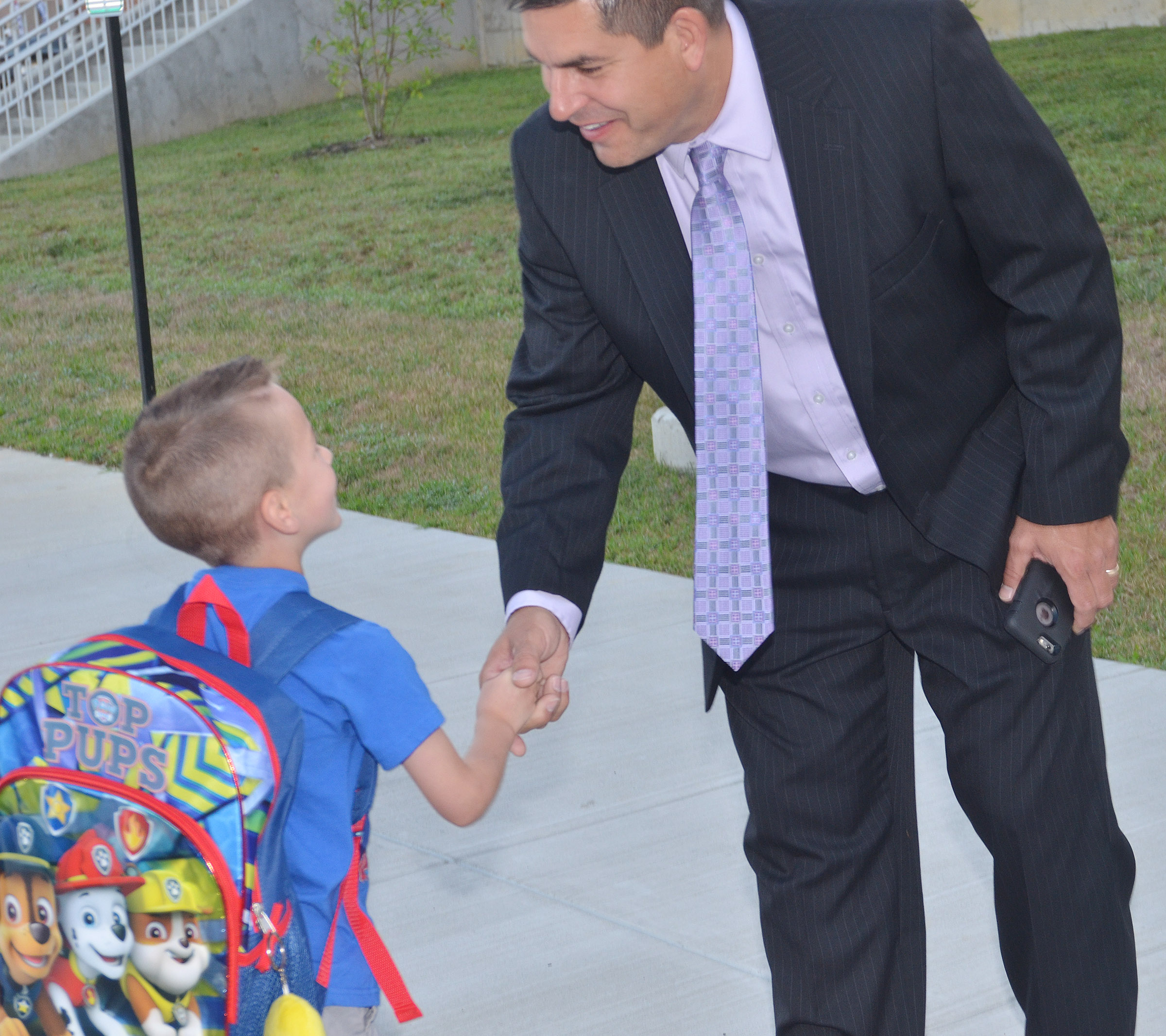 CIS Superintendent Kirby Smith shakes hands with CES kindergartener Cash Davis on the first day of school.