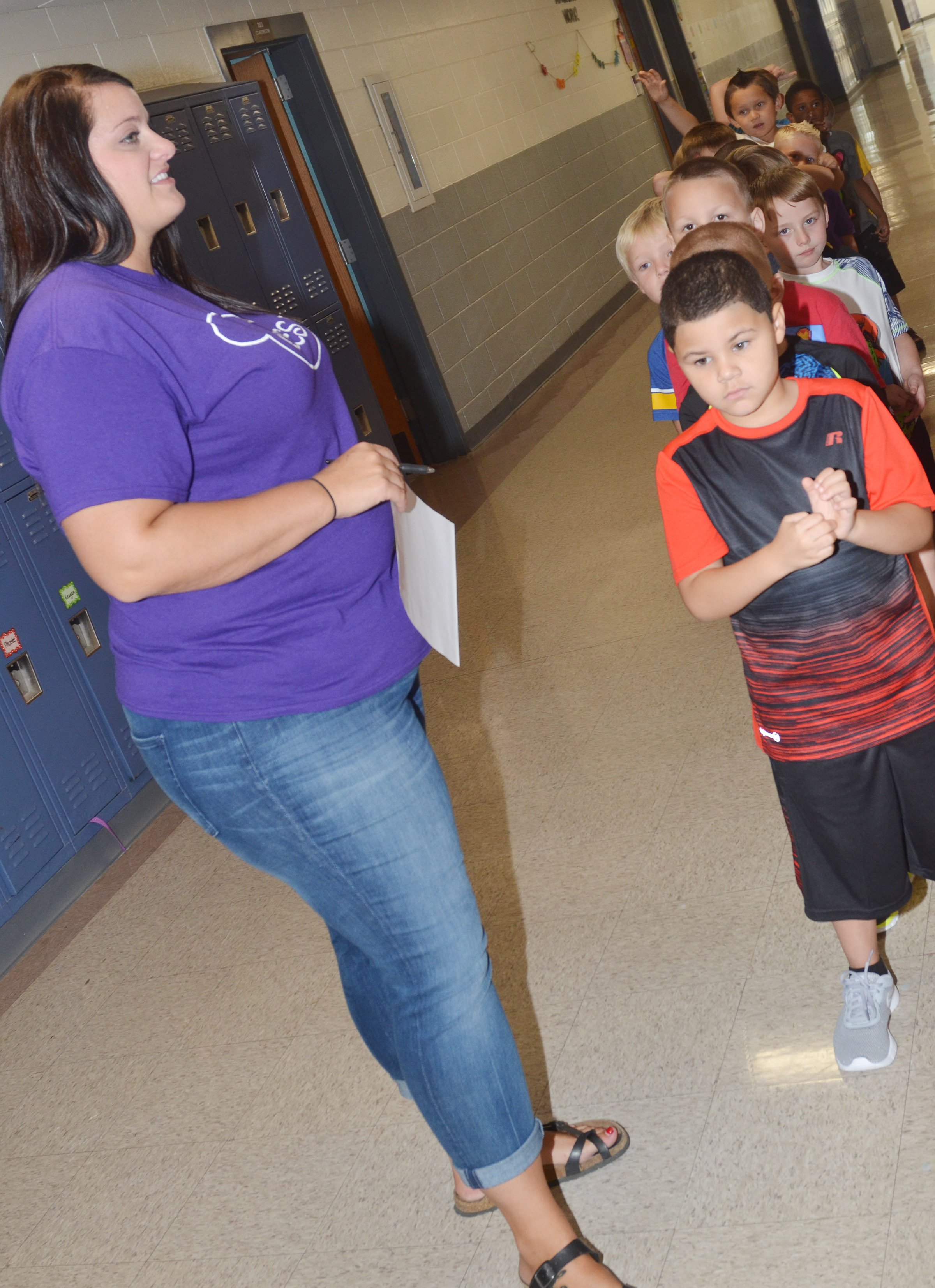 CES first-grade teacher Miriah Cox waits with her students as they take a restroom break.
