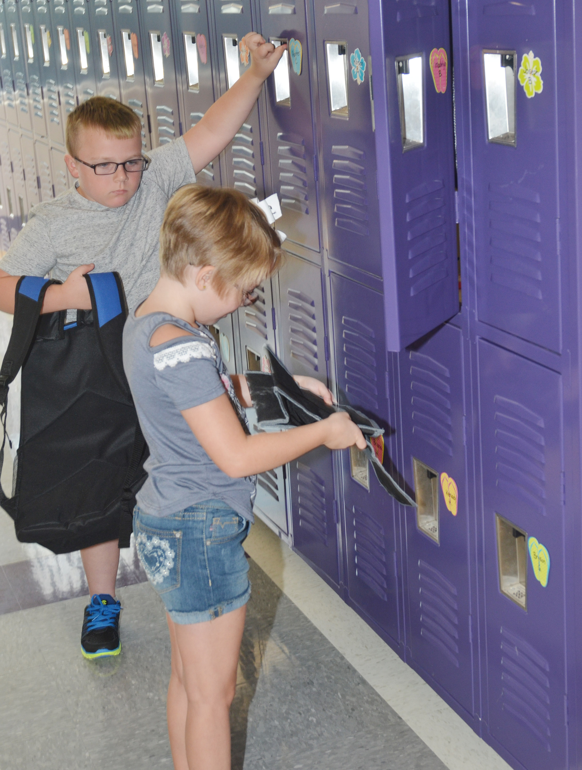 CES second-graders Hunter Clark, at left, and Maddie Brunelle put their supplies in their lockers.