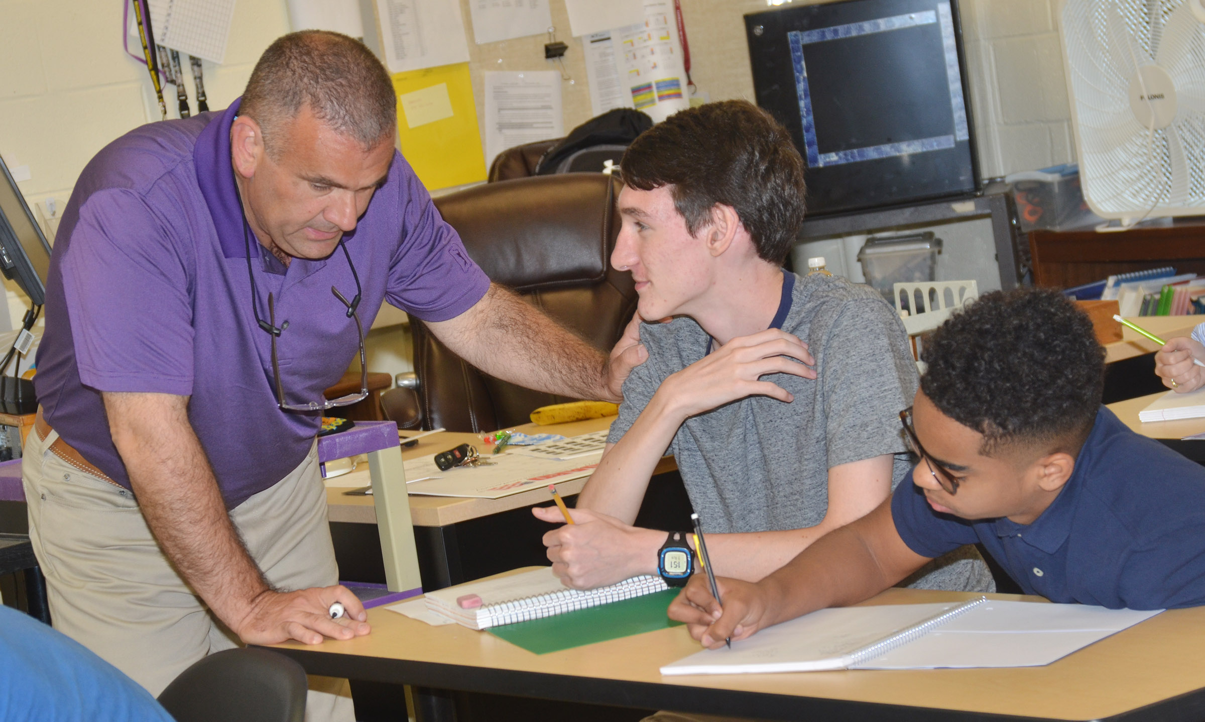 CHS teacher Kevin Rafferty talks with juniors Ian McAninch, center, and Davon Cecil.