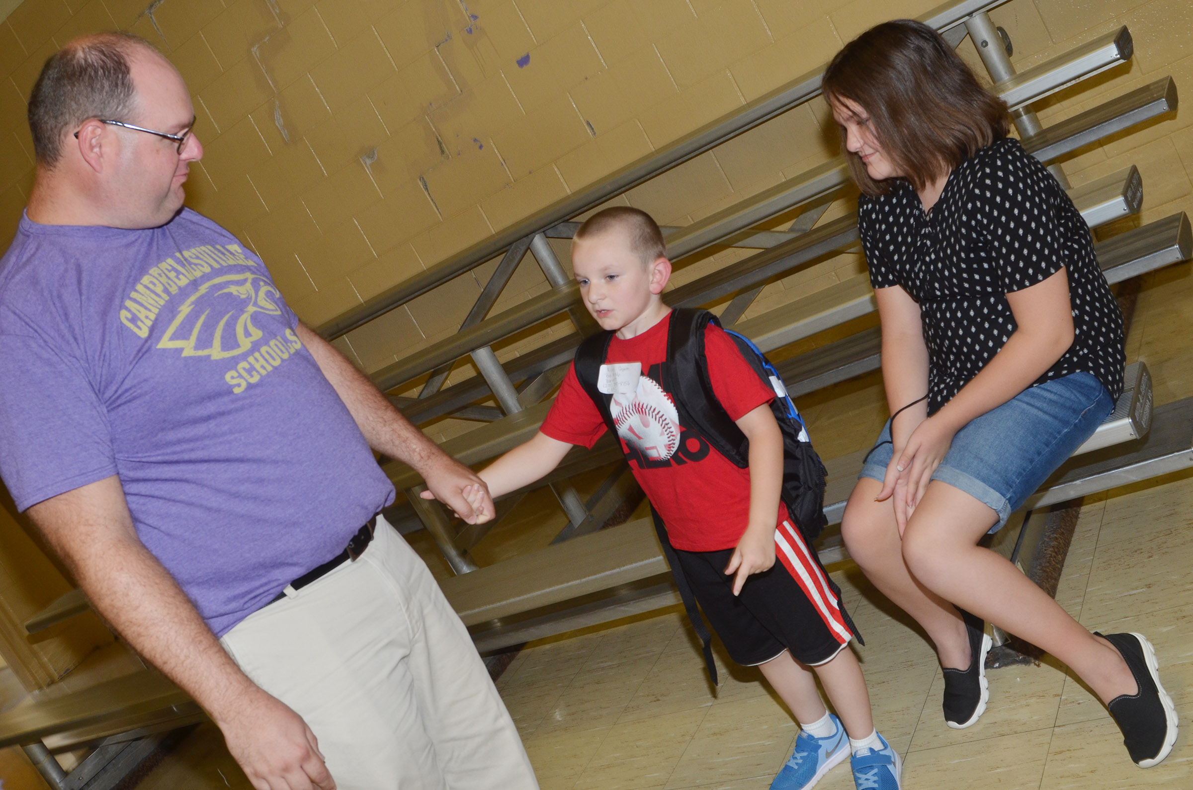 CES kindergartener Ryne Gumm talks to his dad Steven, a teacher at CMS, and sister Savannah, an eighth-grader at CMS, about his first day of school.