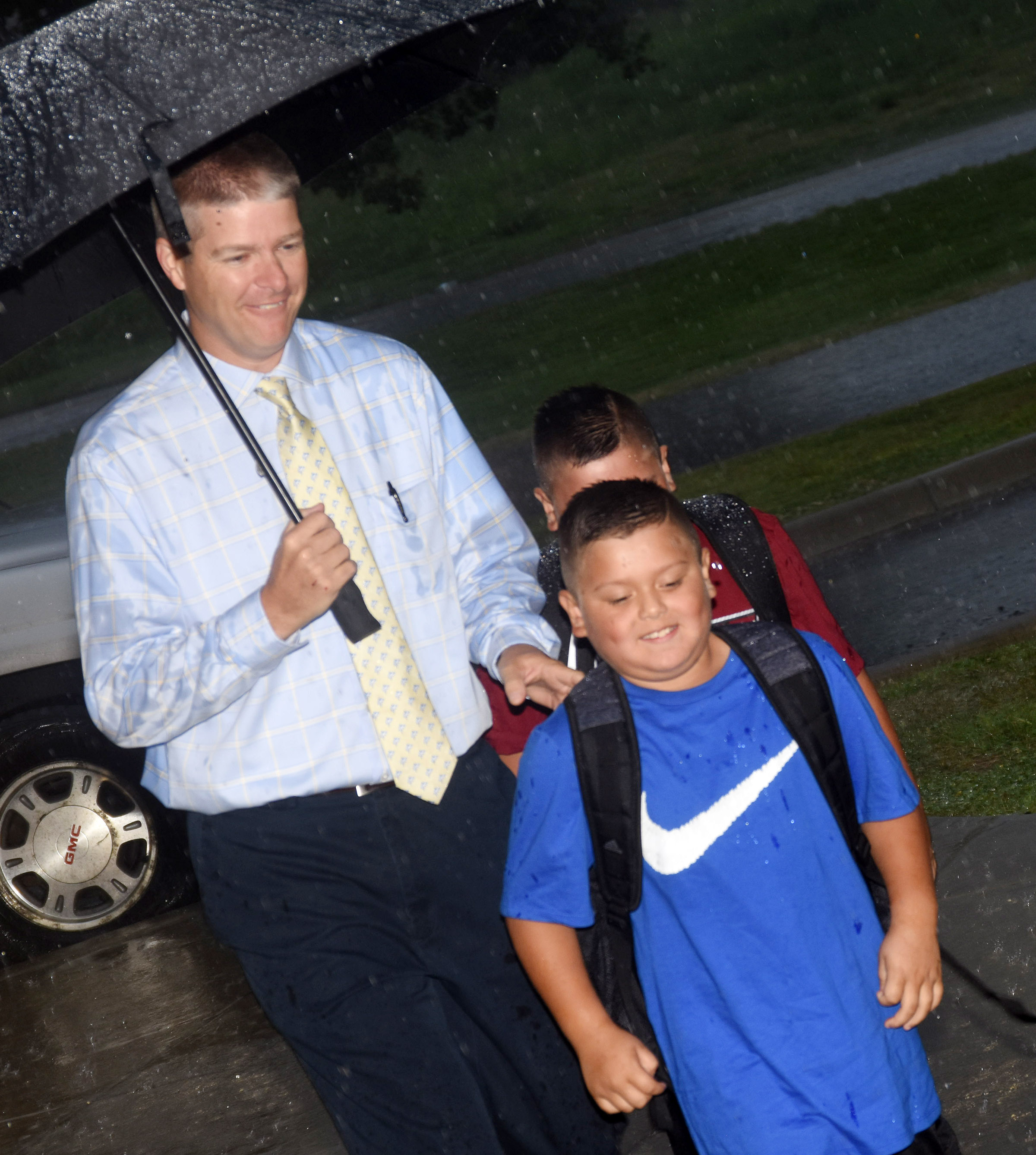 Campbellsville Elementary School Wings Express Director Doug Holmes walks brothers Alex, in front, and Eric Mixtega to school as they begin their third-grade year.