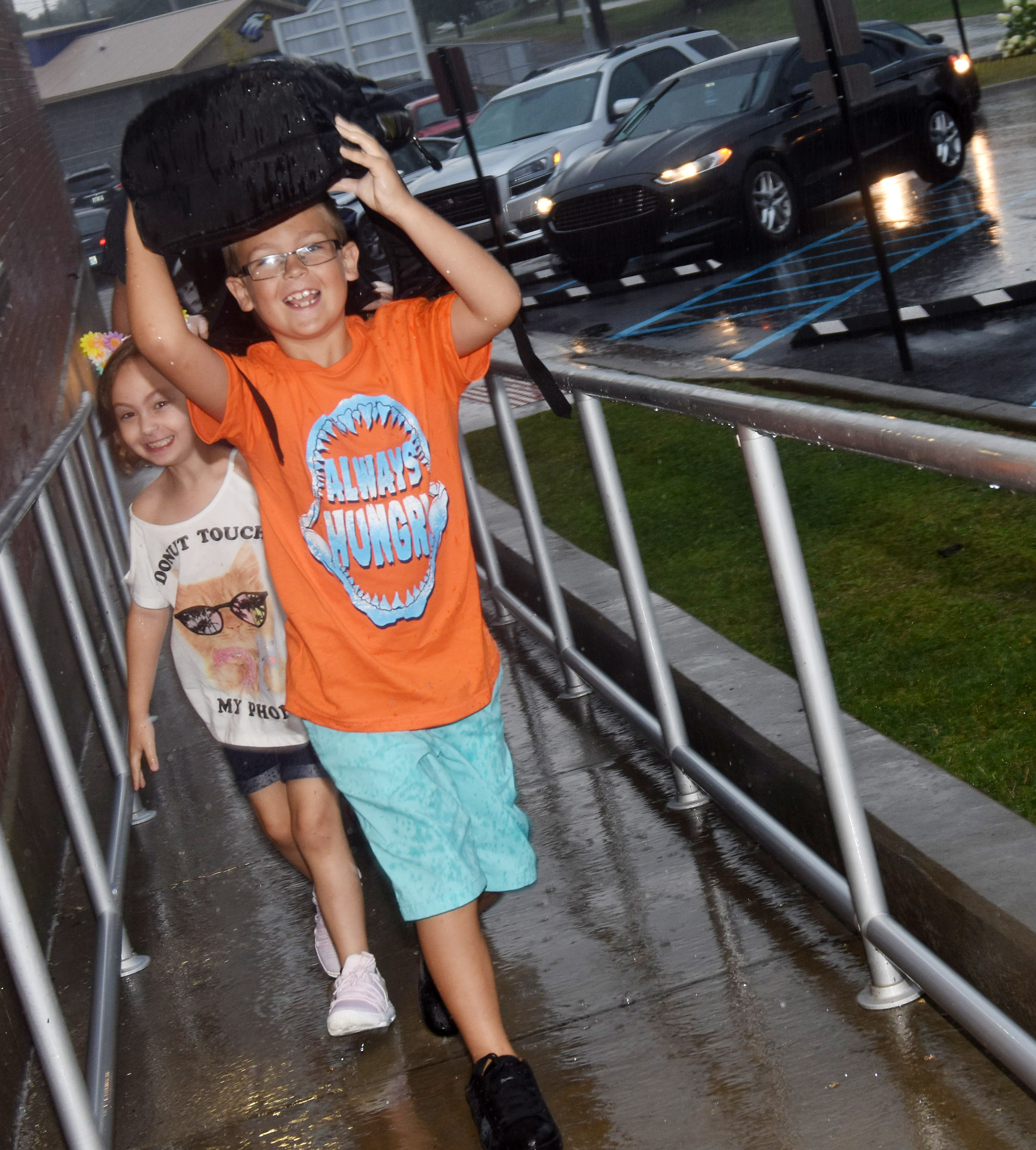 Campbellsville Elementary School third-grader Brendan Martin uses his backpack to shield himself from the rain as he walks in to school.