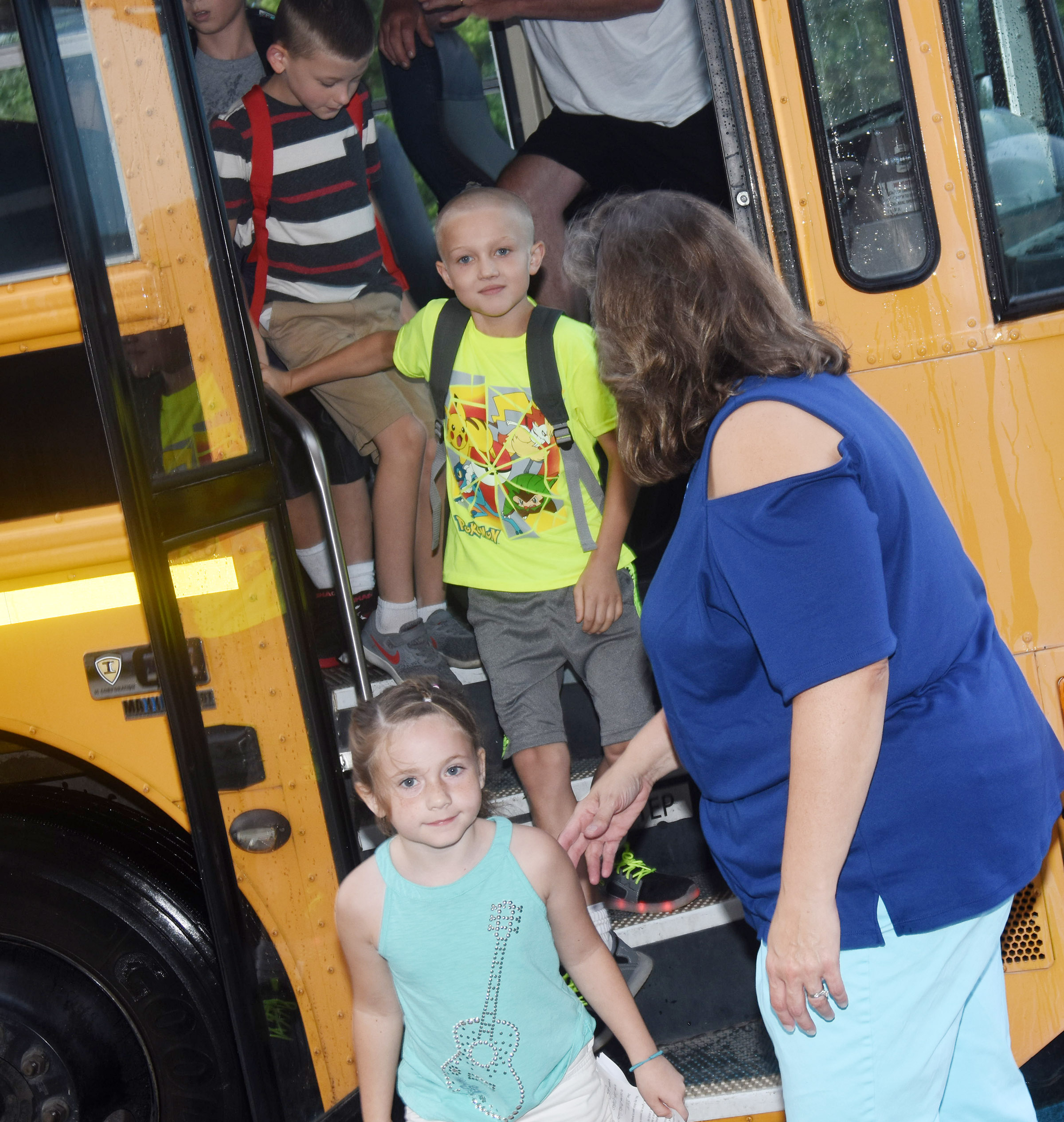 Campbellsville Elementary School music teacher Cyndi Chadwick helps students off the bus as they arrive at school.