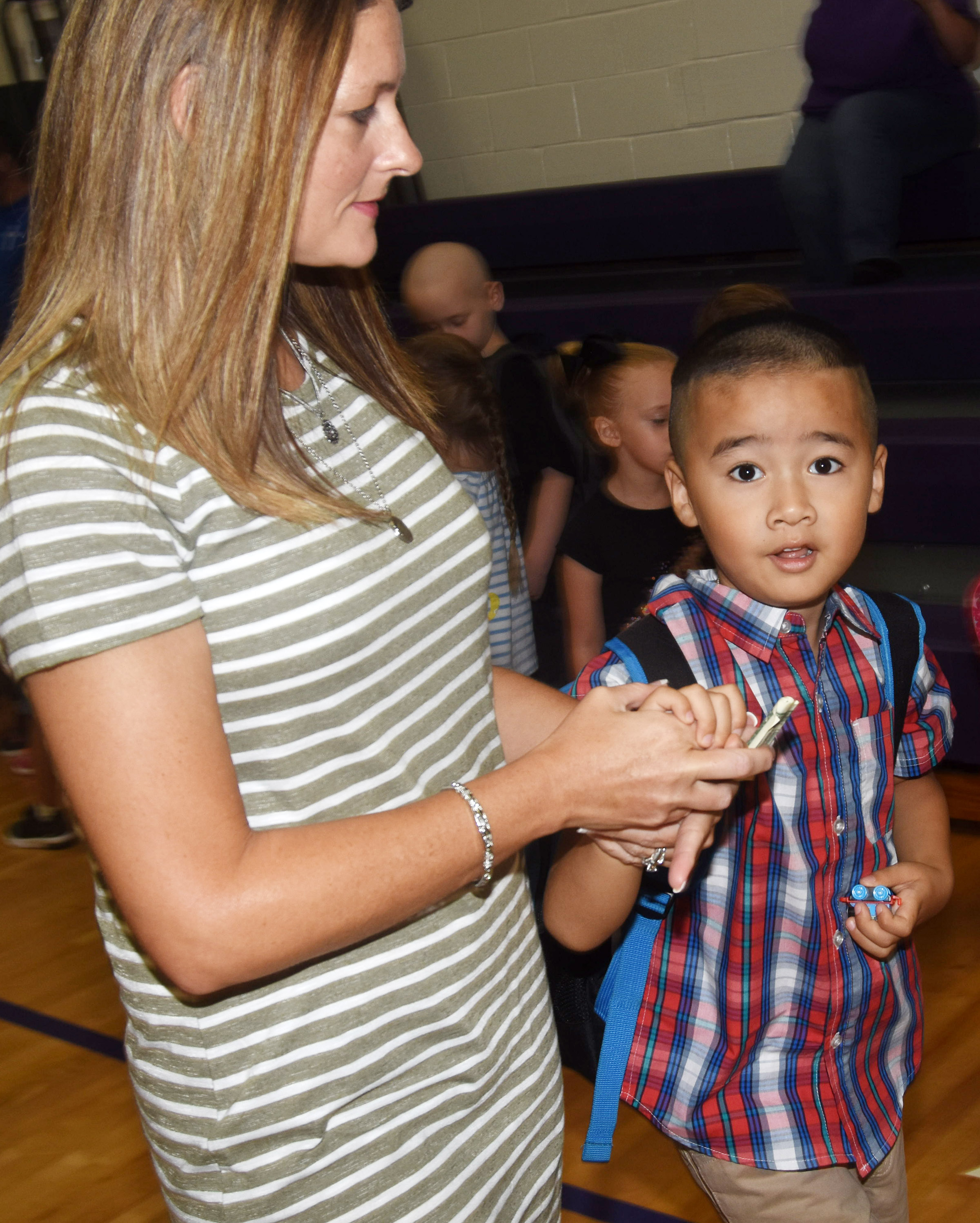 Campbellsville Elementary School kindergartener Minh Turdo walks to his classroom with instructional assistant Tracey Paiz.
