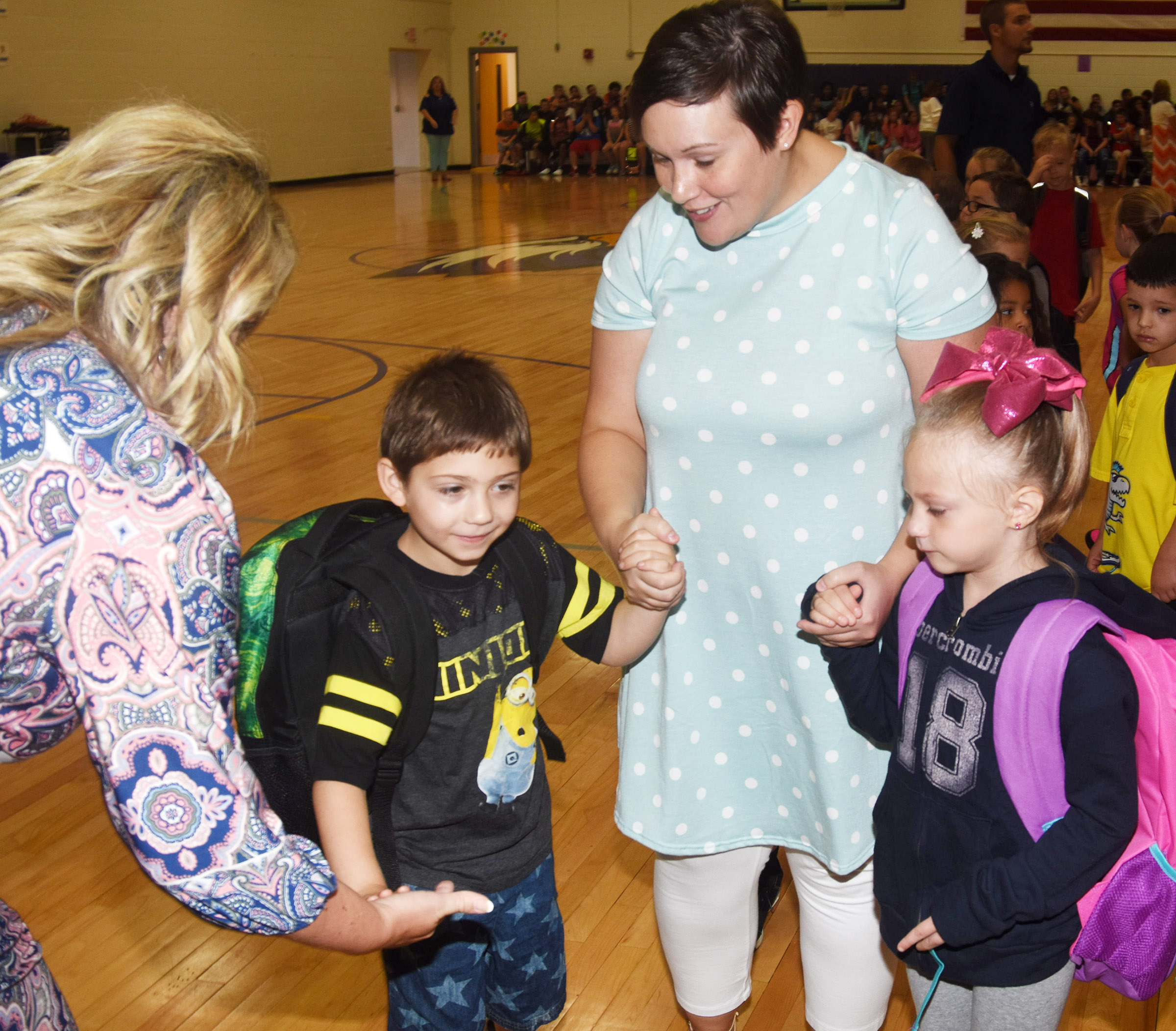 Campbellsville Elementary School first-grade teacher Amanda Barnett greets Principal Elisha Rhodes as she holds hands with first-graders Josiah Dean and Amary Tompkins.