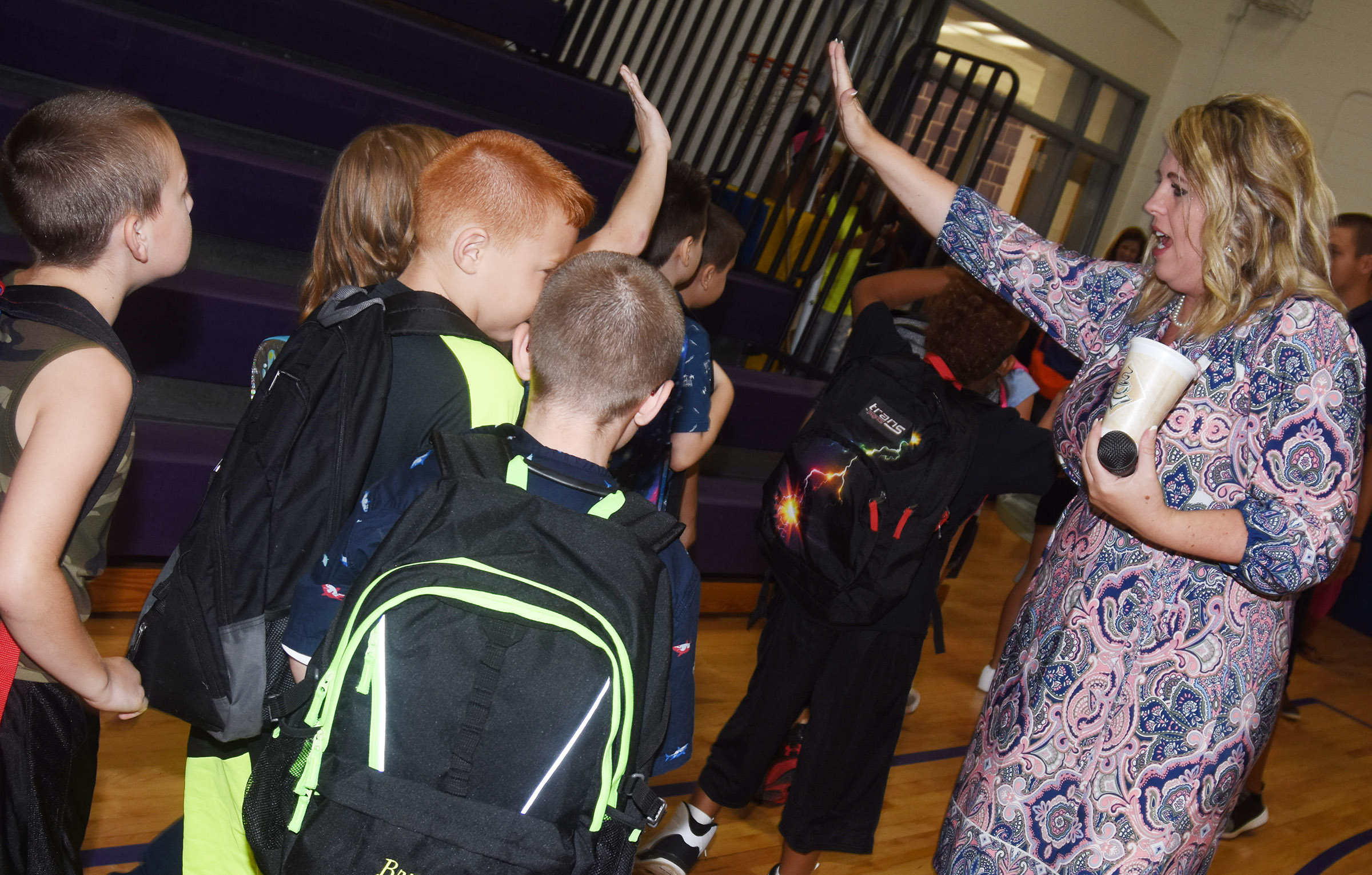 Campbellsville Elementary School Principal Elisha Rhodes high-fives students as they walk to their classmates.