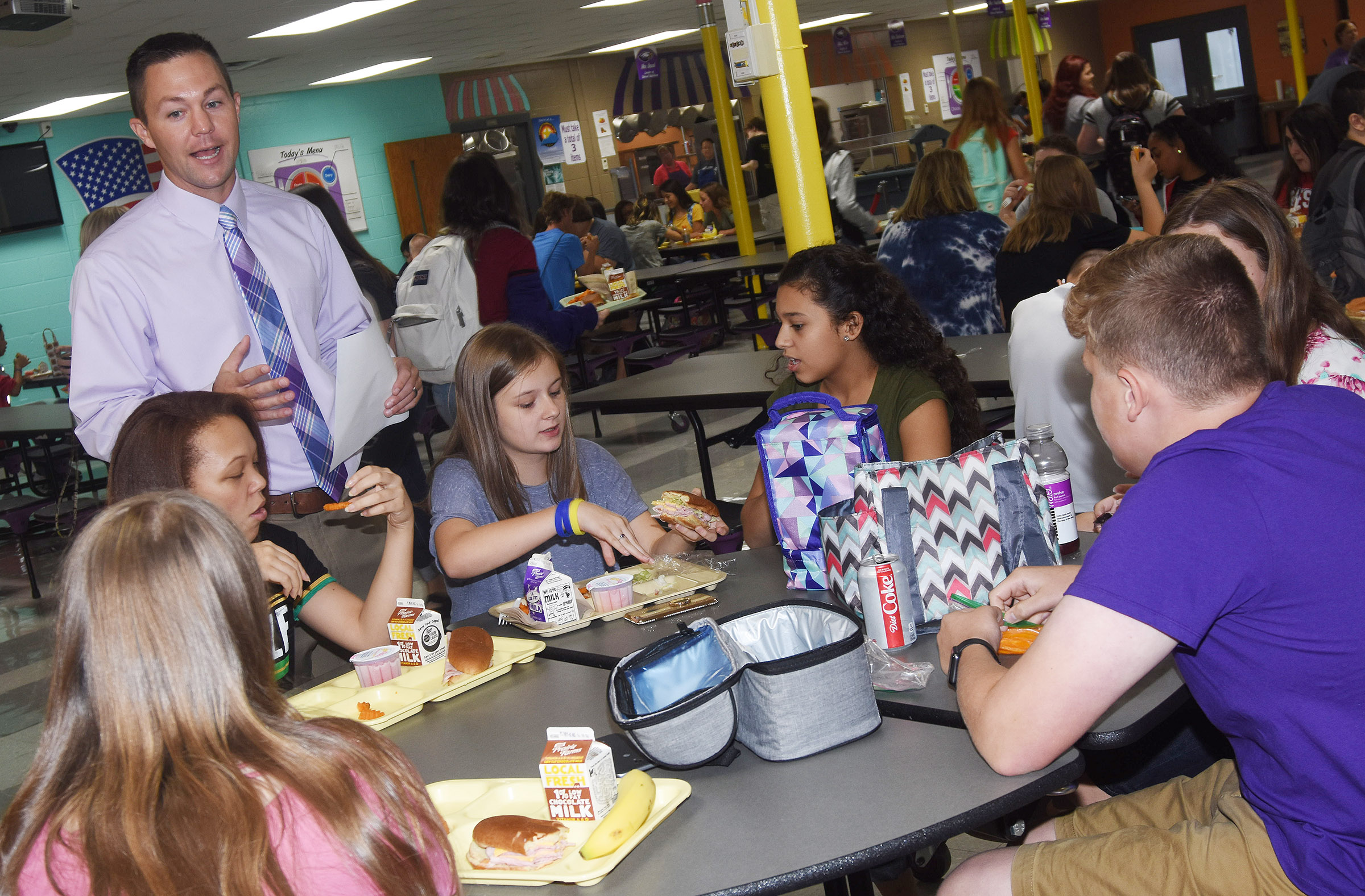 Campbellsville High School Principal Weston Jones talks to his students about their schedules as they enjoy their lunch.
