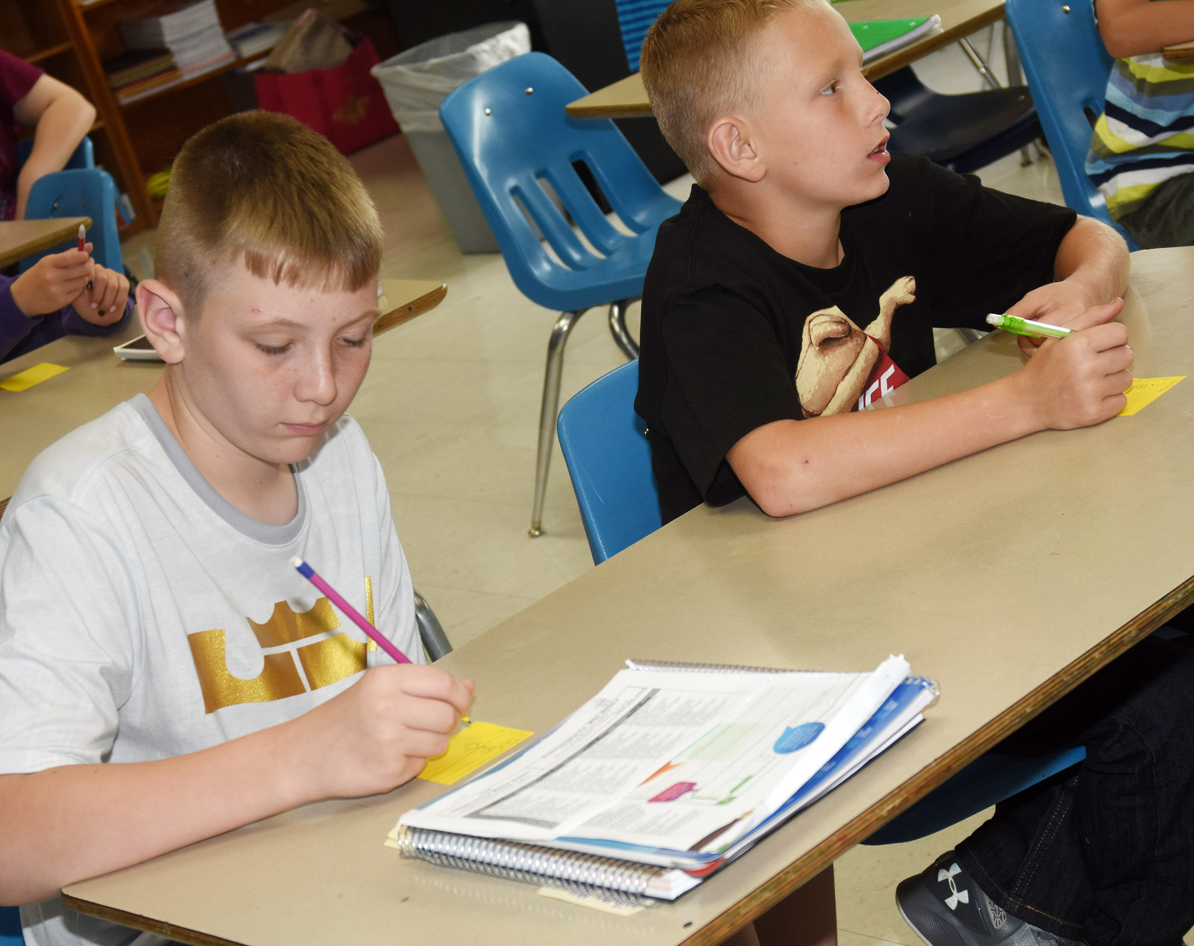 Campbellsville Middle School sixth-graders Kaleb Miller, at left, and Arthur Singleton answer questions in their math class.