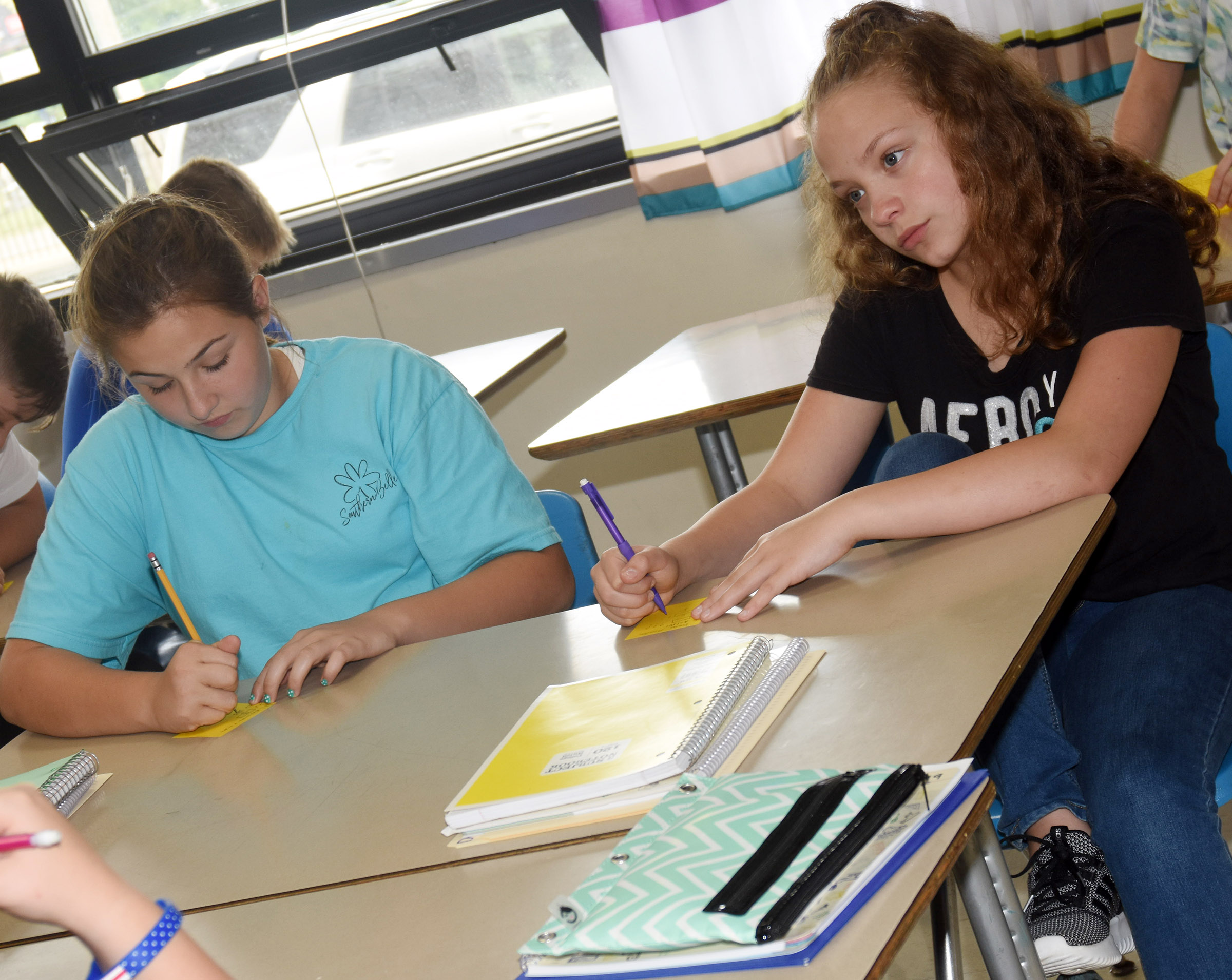 Campbellsville Middle School sixth-graders Riley Newton, at left, and Deanna Reardon answer questions in their math class.