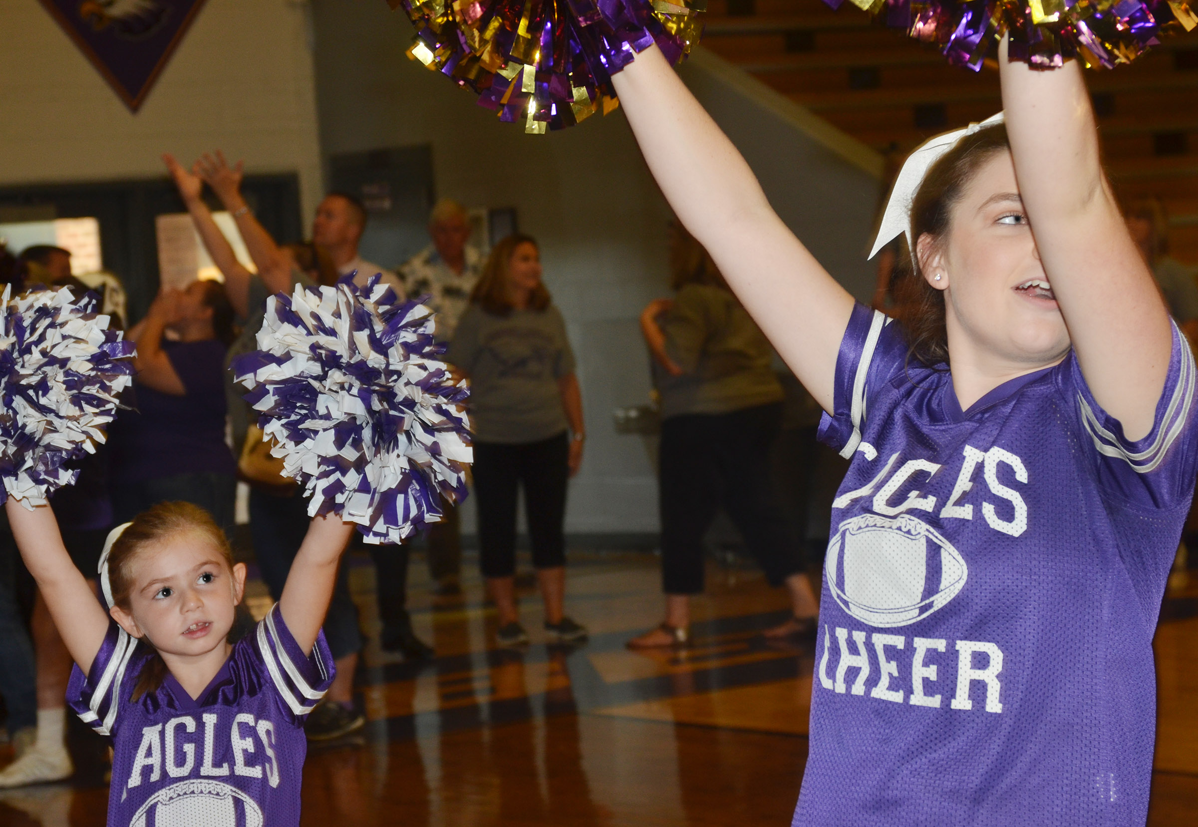 CES second-grader Lainey Price cheers with CHS sophomore Sydney Wilson.