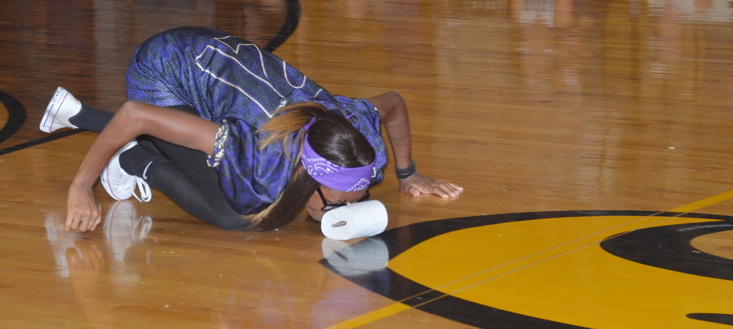 CMS eighth-grader Bri Gowdy moves a roll of tissue paper down the gym floor with her nose while competing in a spirit game.