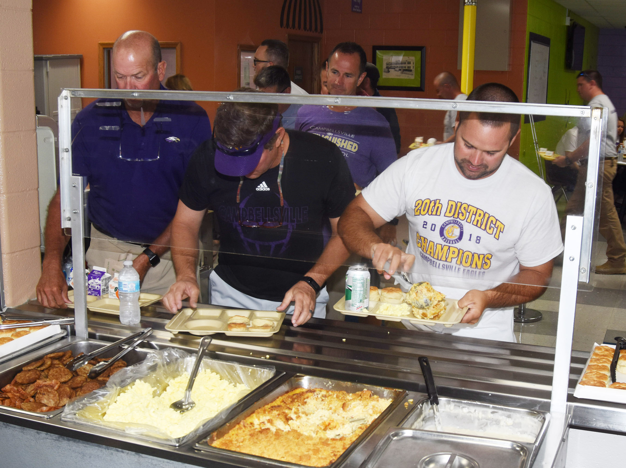From left, Campbellsville High School Athletic Director Tim Davis and teachers Herb Wiseman and Blake Milby serve themselves during the opening day breakfast.