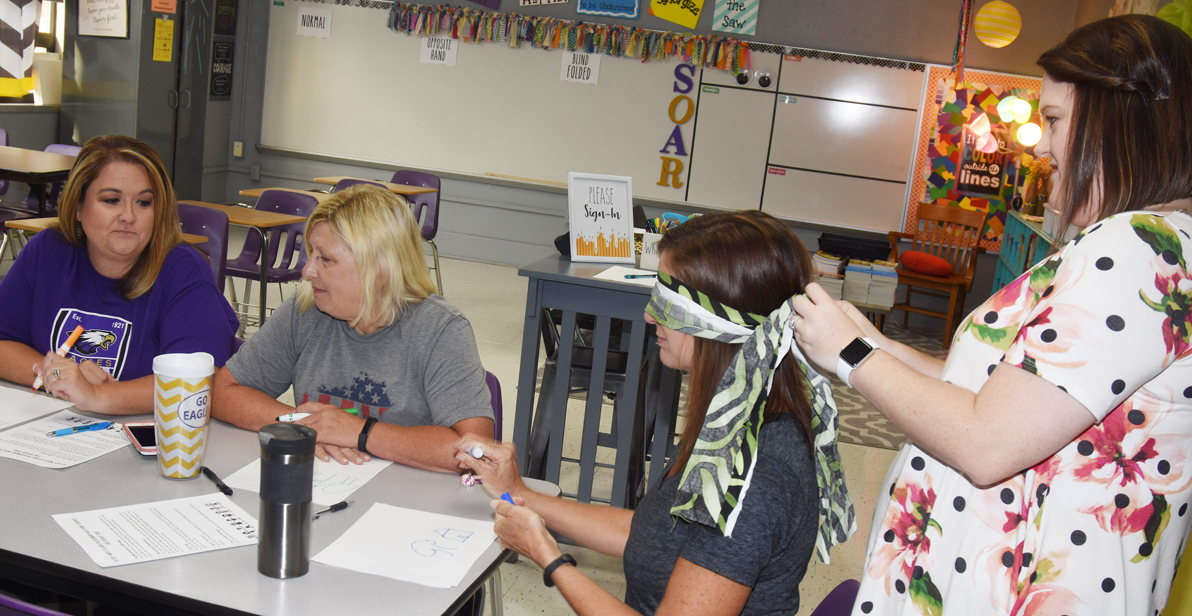 CMS teacher Paige Cook blindfolds speech pathologist Christi Kidwell in an activity during a session on building relationships with students. In the activity, teachers were asked to perform writing tasks while being blindfolded and with their non-dominant hand.