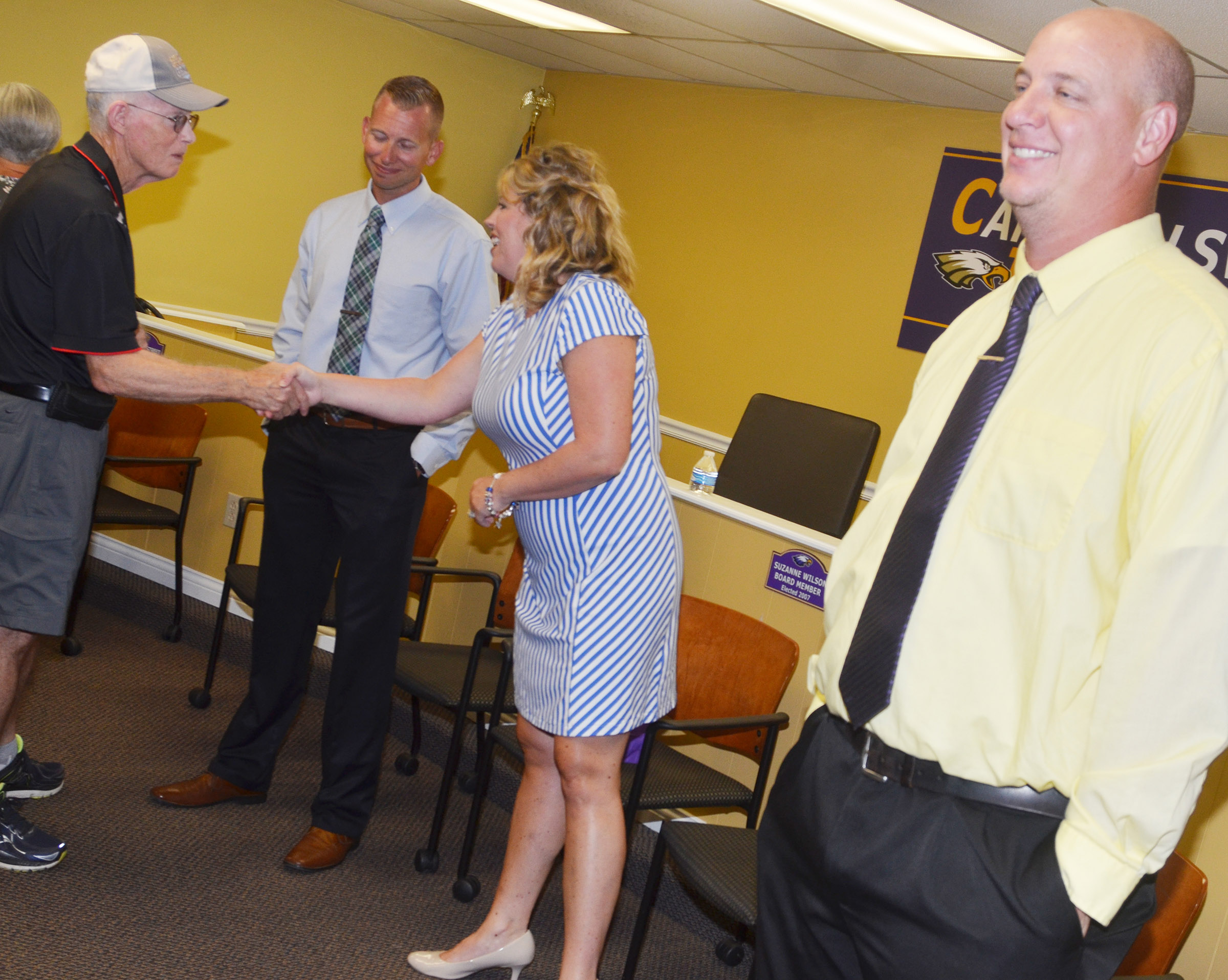 From left, CMS Principal Zach Lewis, CES Principal Elisha Rhodes and CHS Principal David Petett receive congratulations from Phil Allan Bertram.