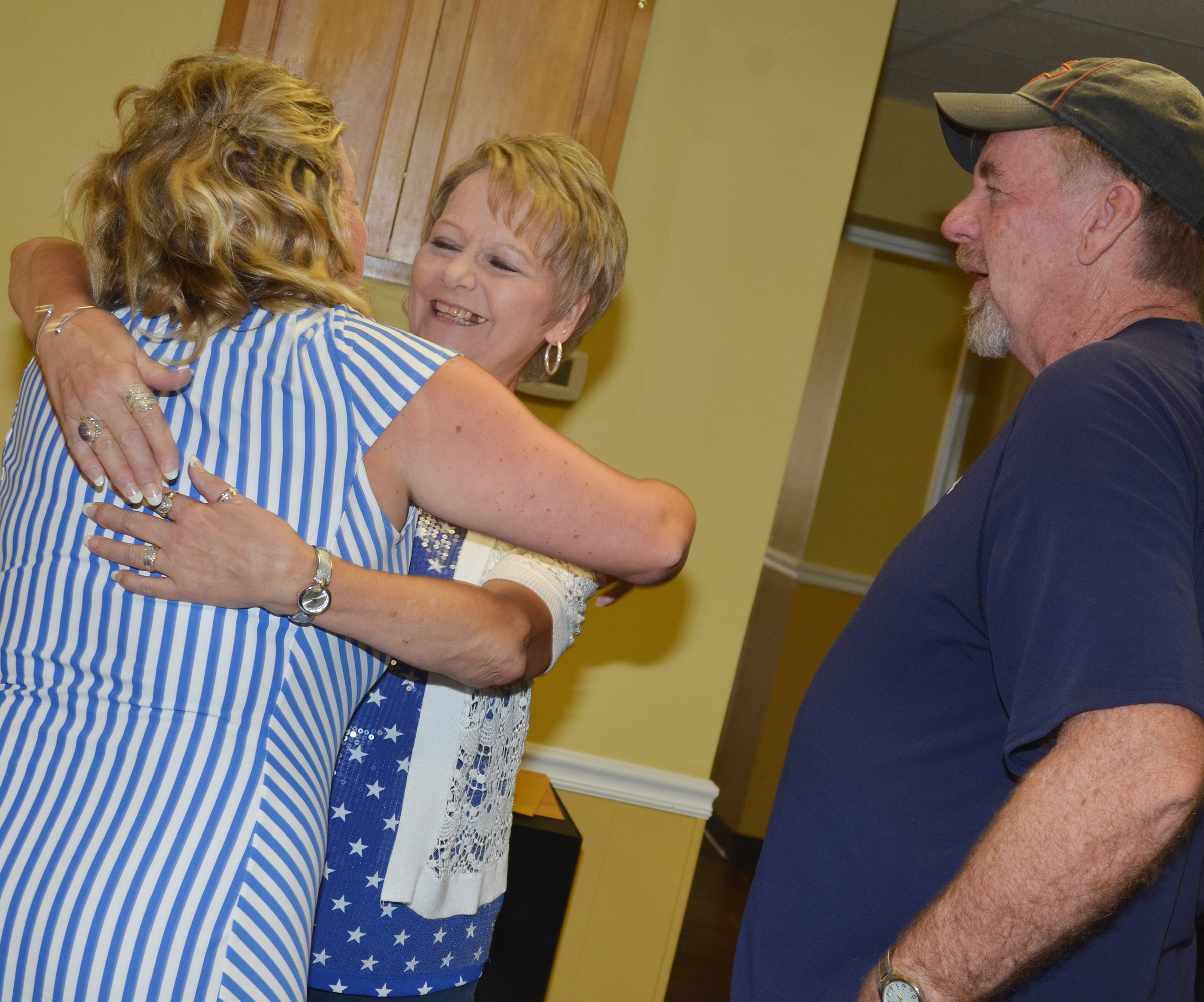 CES Principal Elisha Rhodes receives a congratulatory hug from her mother-in-law, Sherri. At right is Rhodes's father-in-law, Dean.