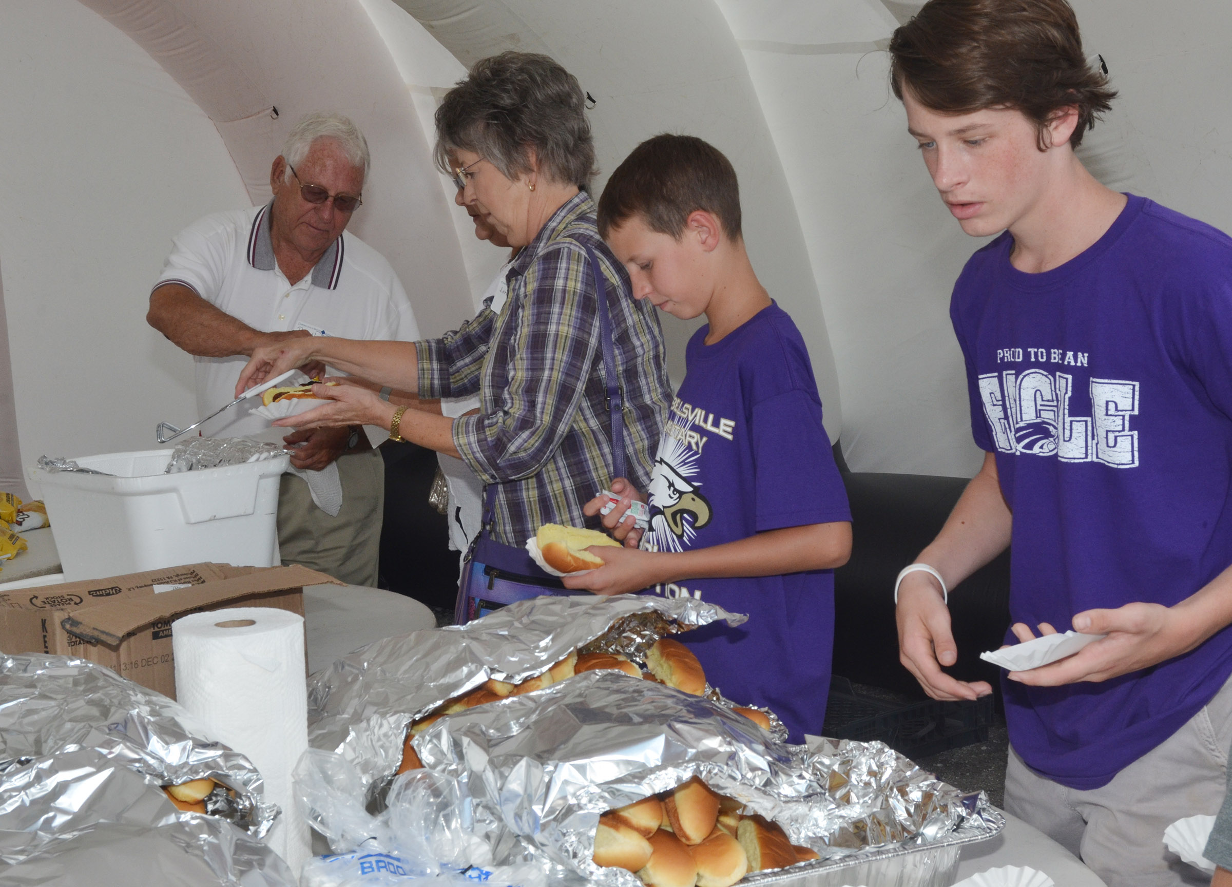 CES fifth-grader Rowan Petett, at left, and CMS seventh-grader Seth Hash enjoy hot dogs.