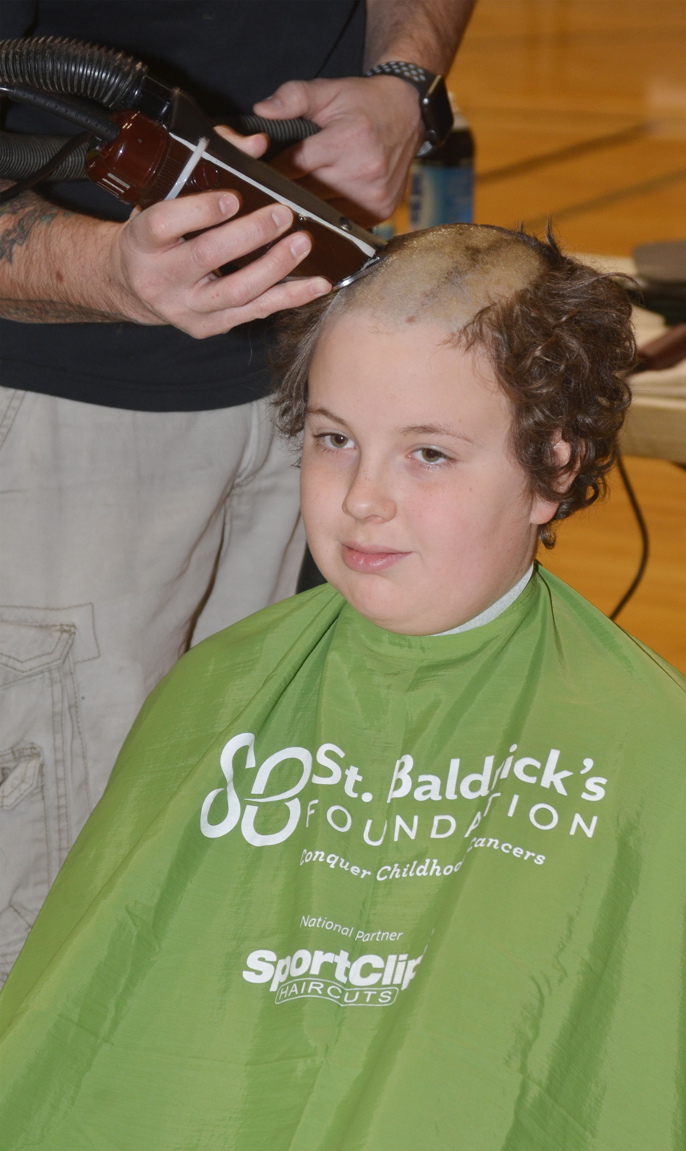 CMS fifth-grader Daniel Caton has his head shaved to raise money for children's cancer research.