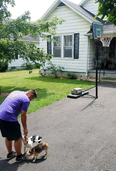 "Campbellsville High School Principal Mark ""Shiny"" Kearney pets a student's dogs at their home."