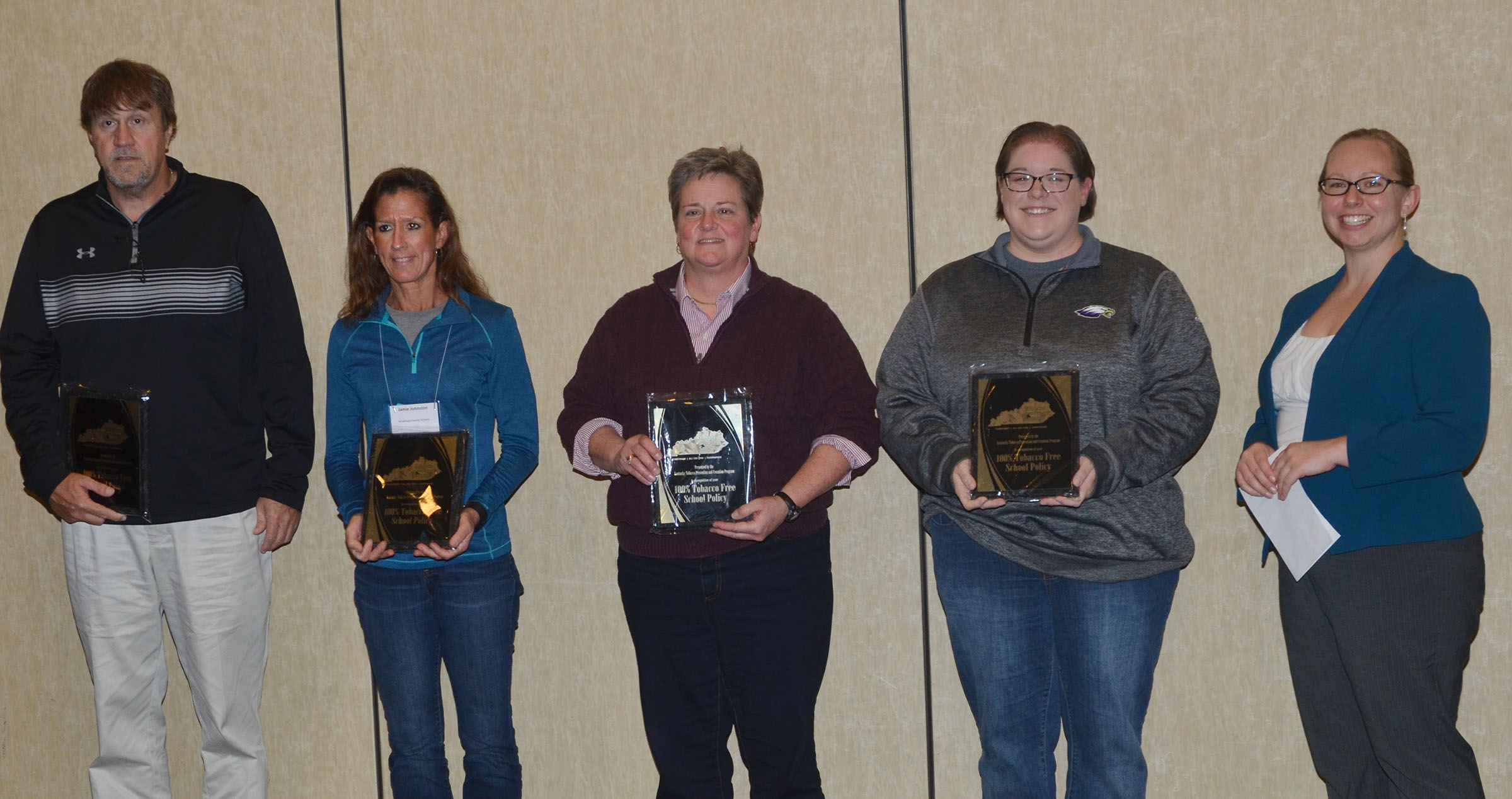 Calen McKinney, CIS public information officer, second from right, accepts the award on the District's behalf. At right is Elizabeth Anderson-Hoagland, youth tobacco prevention coordinator for the Kentucky Tobacco Prevention and Cessation Program, who honored the Kentucky public school districts that adopted a tobacco-free policy in 2016.