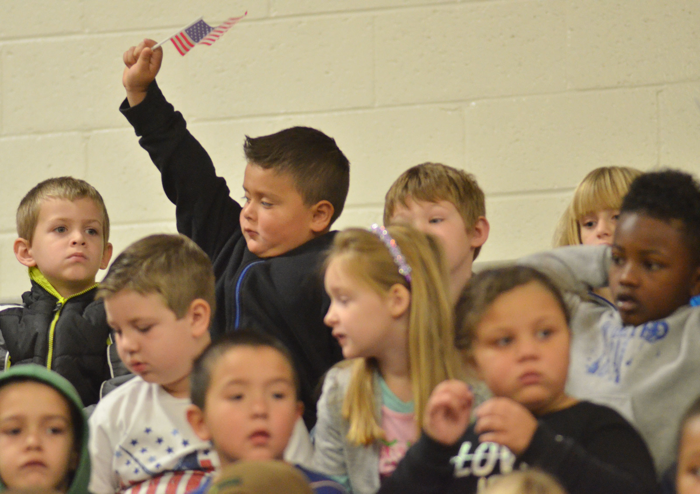 CES first-grader Eric Mixtega waves the American flag.