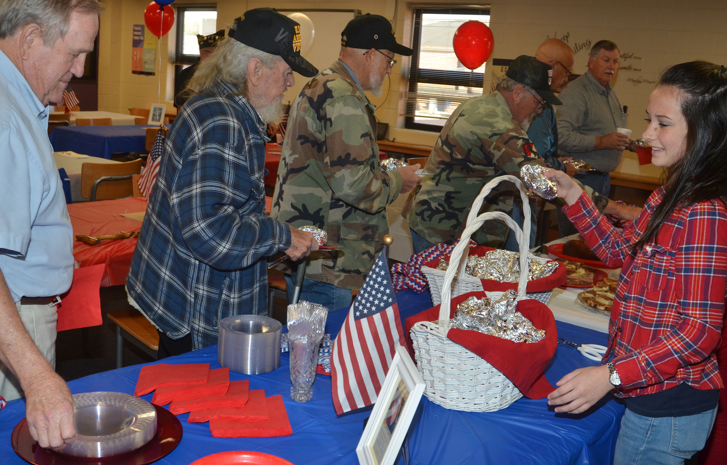 CMS seventh-grader Sarah Adkins, a member of her school's Lighthouse Team, serves veterans at a breakfast in their honor.