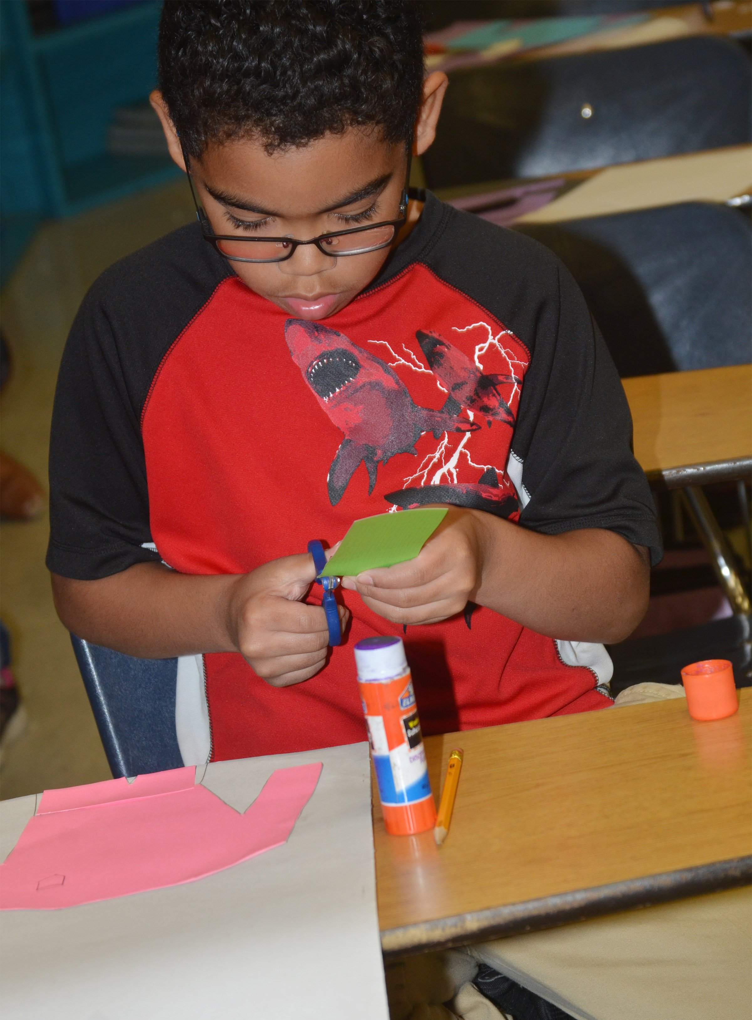 CMS fourth-grader Gabriel Noyola cuts out construction paper to make his jockey.
