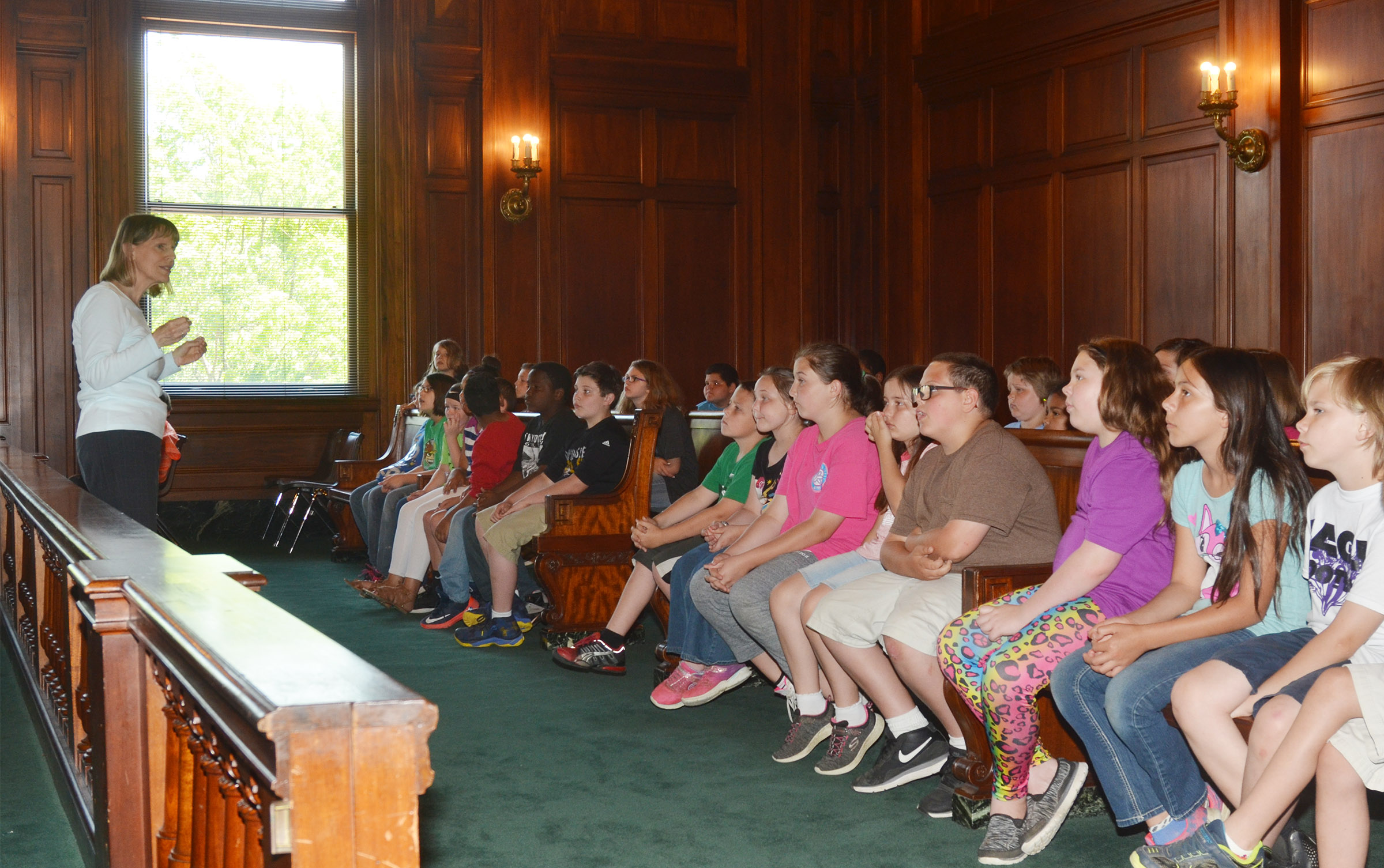 Capitol tour guide Annie Denny talks to CMS fourth-graders about the Kentucky Supreme Court chambers.