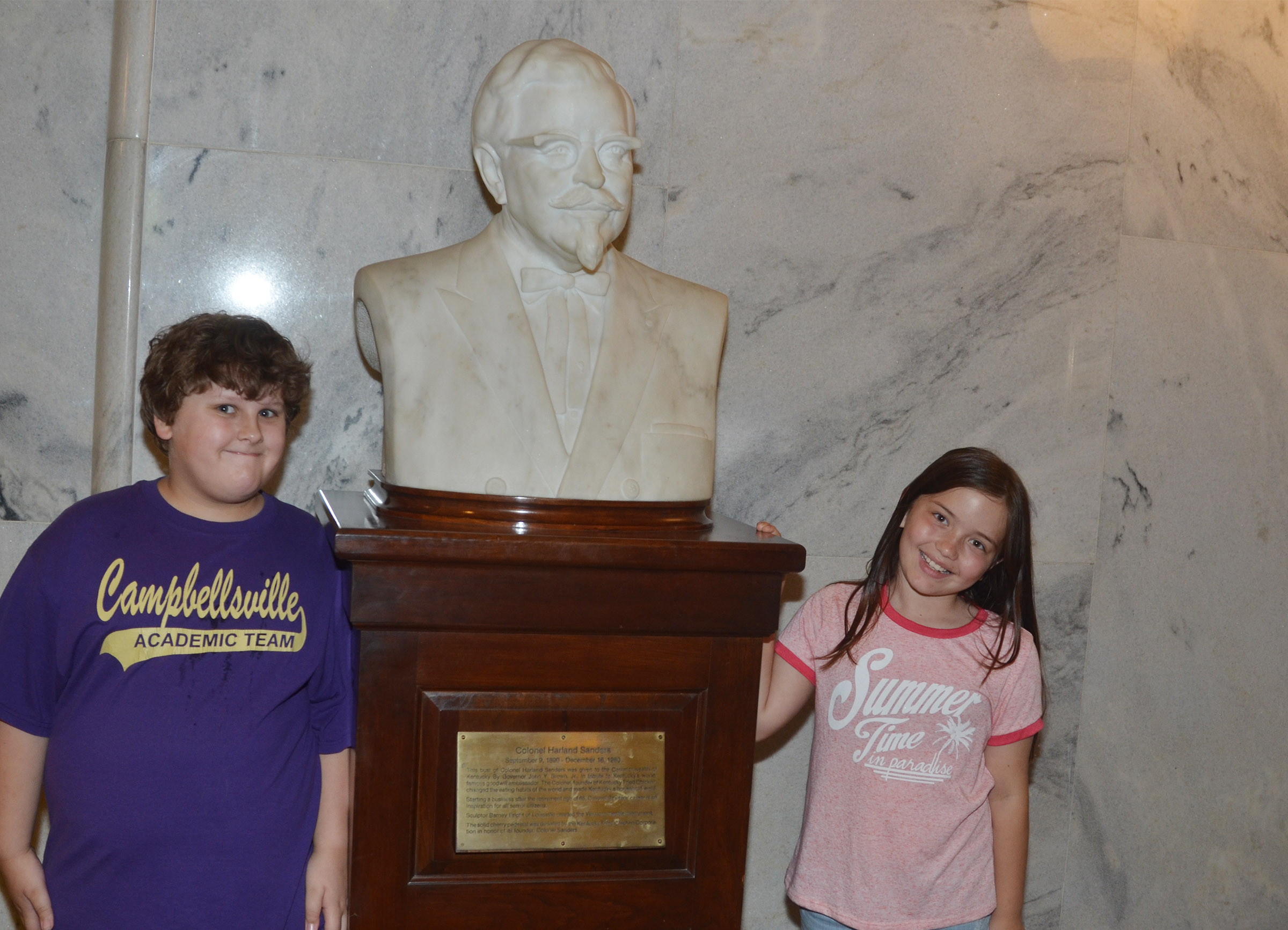 CMS fourth-graders Zeke Harris, at left, and Kate Billeter pose for a photo with a statue of Colonel Harland Sanders.