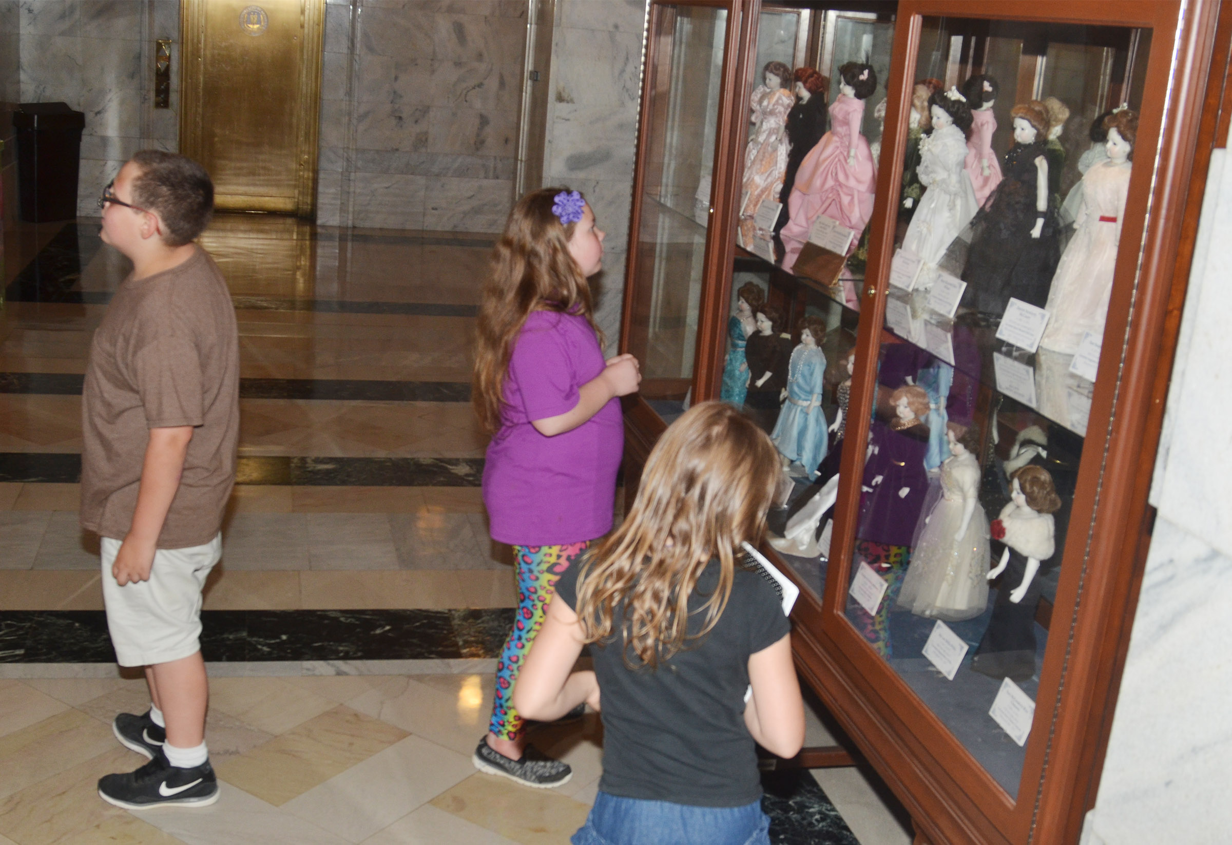CMS fourth-graders look at the historic dolls on display at the state capitol.