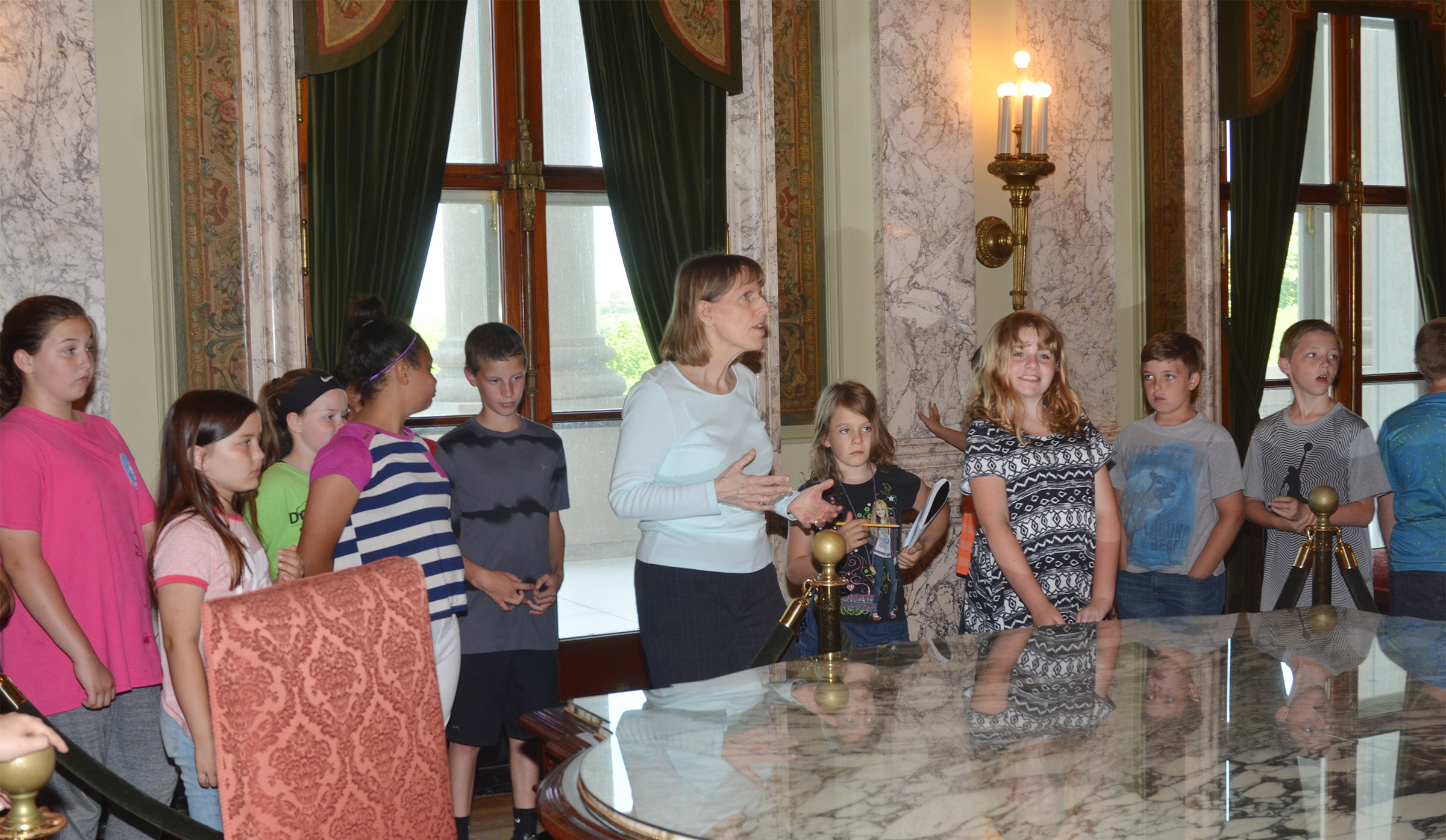 Capitol tour guide Annie Denny talks to CMS fourth-graders about a historic reception room at the capitol building.