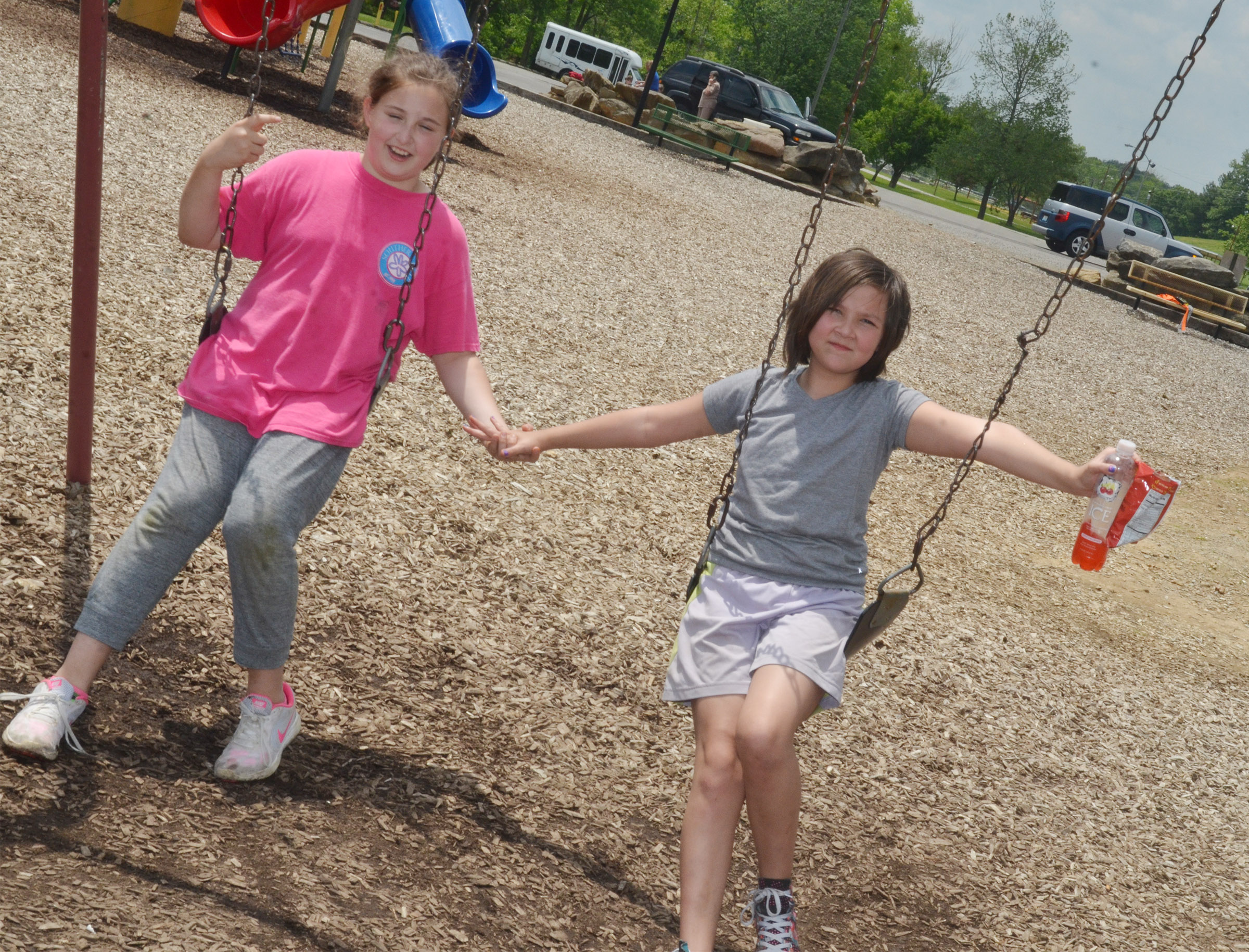 CMS fourth-graders Riley Newton, at left, and Cassie Crick swing together.