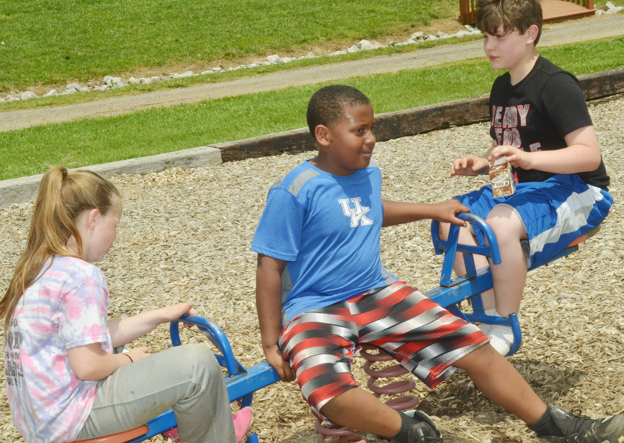 CMS fourth-graders Miley Hash, at left, and Andrew Mardis play on the teeter totter as KeKe Miller sits in the middle.