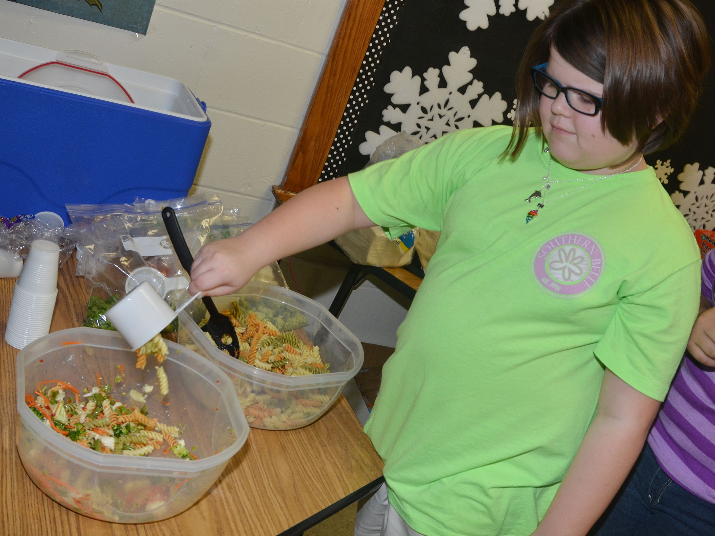CMS fourth-grader Keeley Dicken adds noodles to the class's pasta salad.
