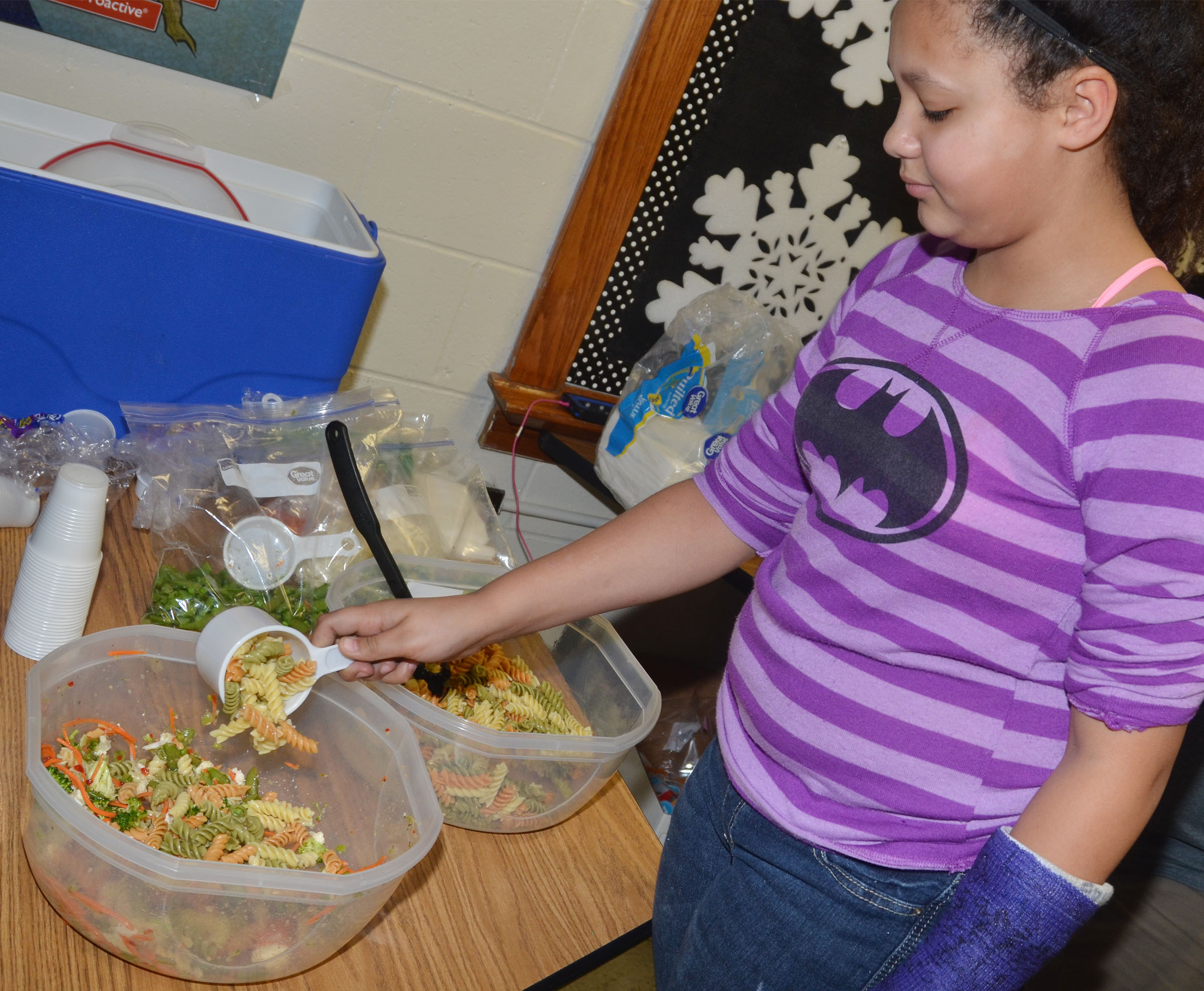 CMS fourth-grader Kenya Bridgewater adds noodles to the class's pasta salad.