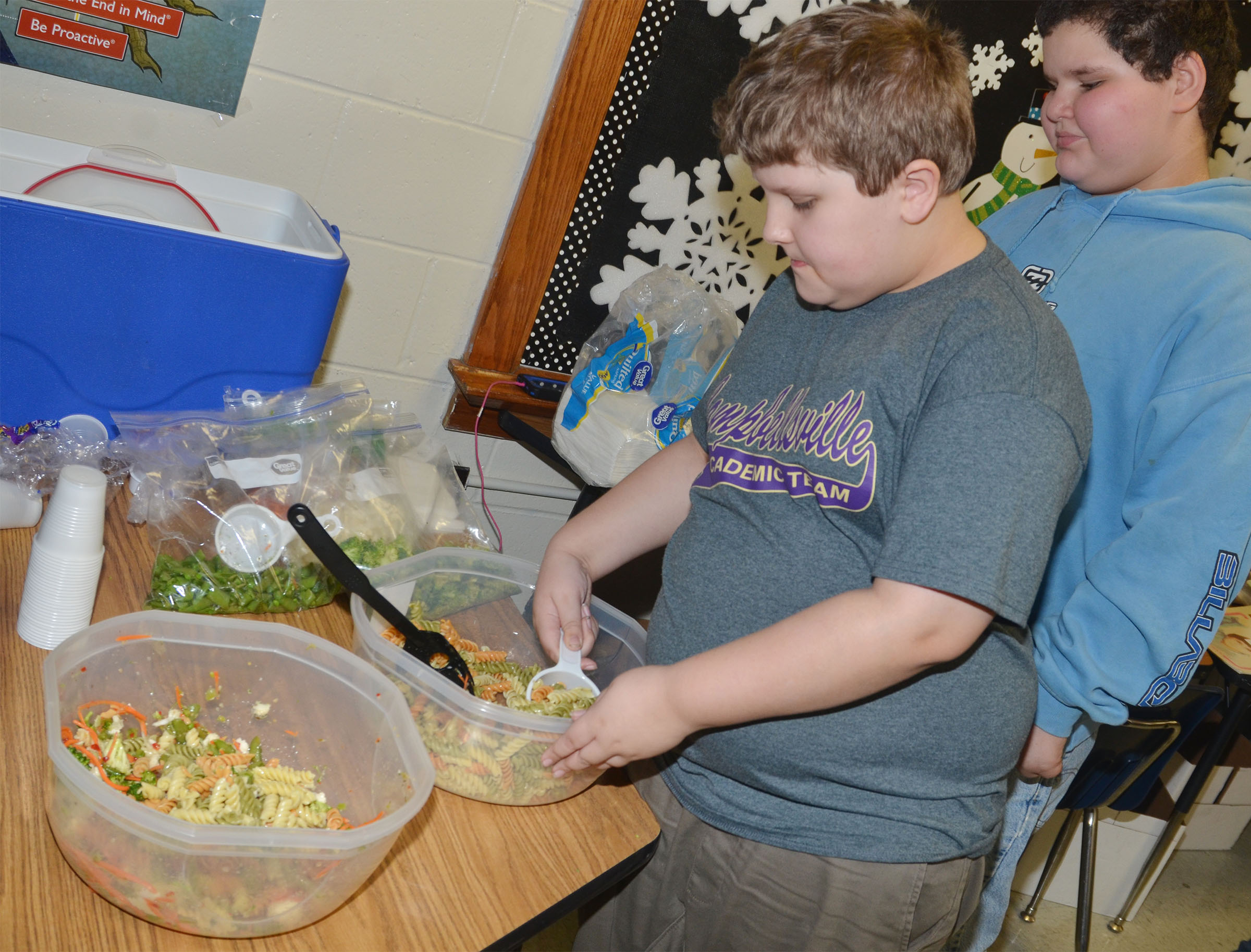 CMS fourth-grader Zeke Harris adds noodles to the class's pasta salad, as Steven Miller waits his turn.