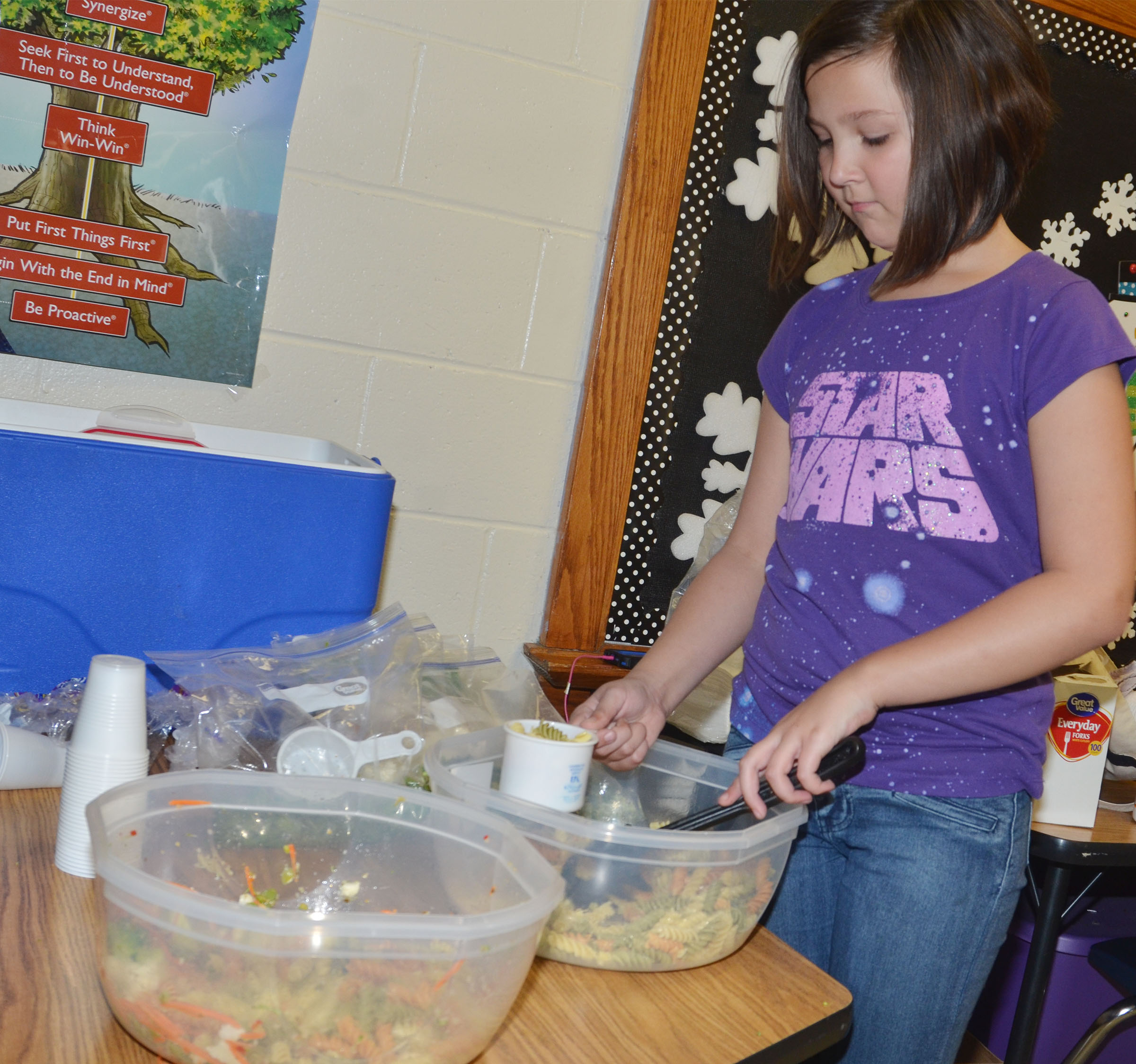 CMS fourth-grader Cassie Crick adds noodles to the class's pasta salad.