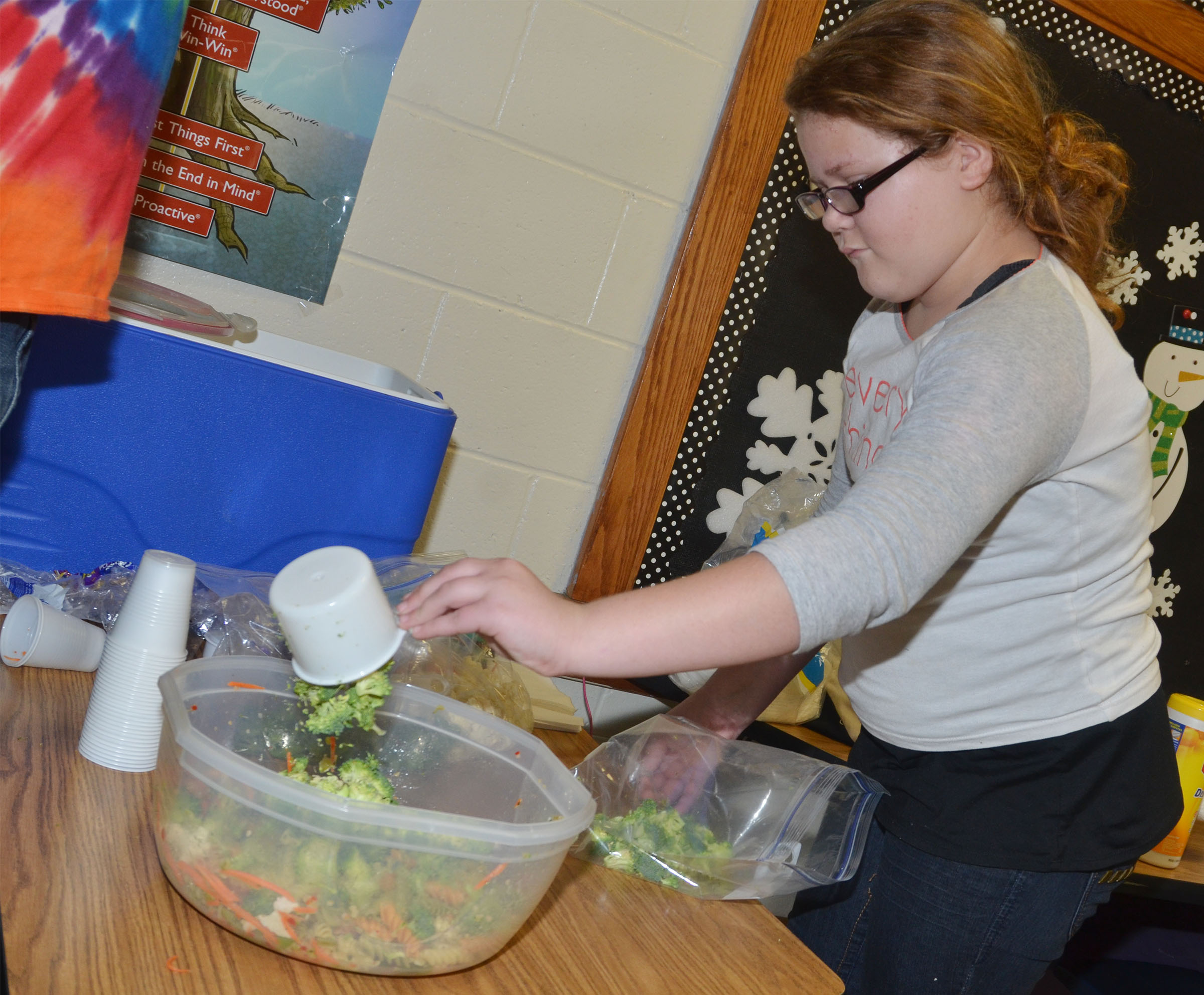 CMS fourth-grader Carmen Gurley adds broccoli to the class's pasta salad.