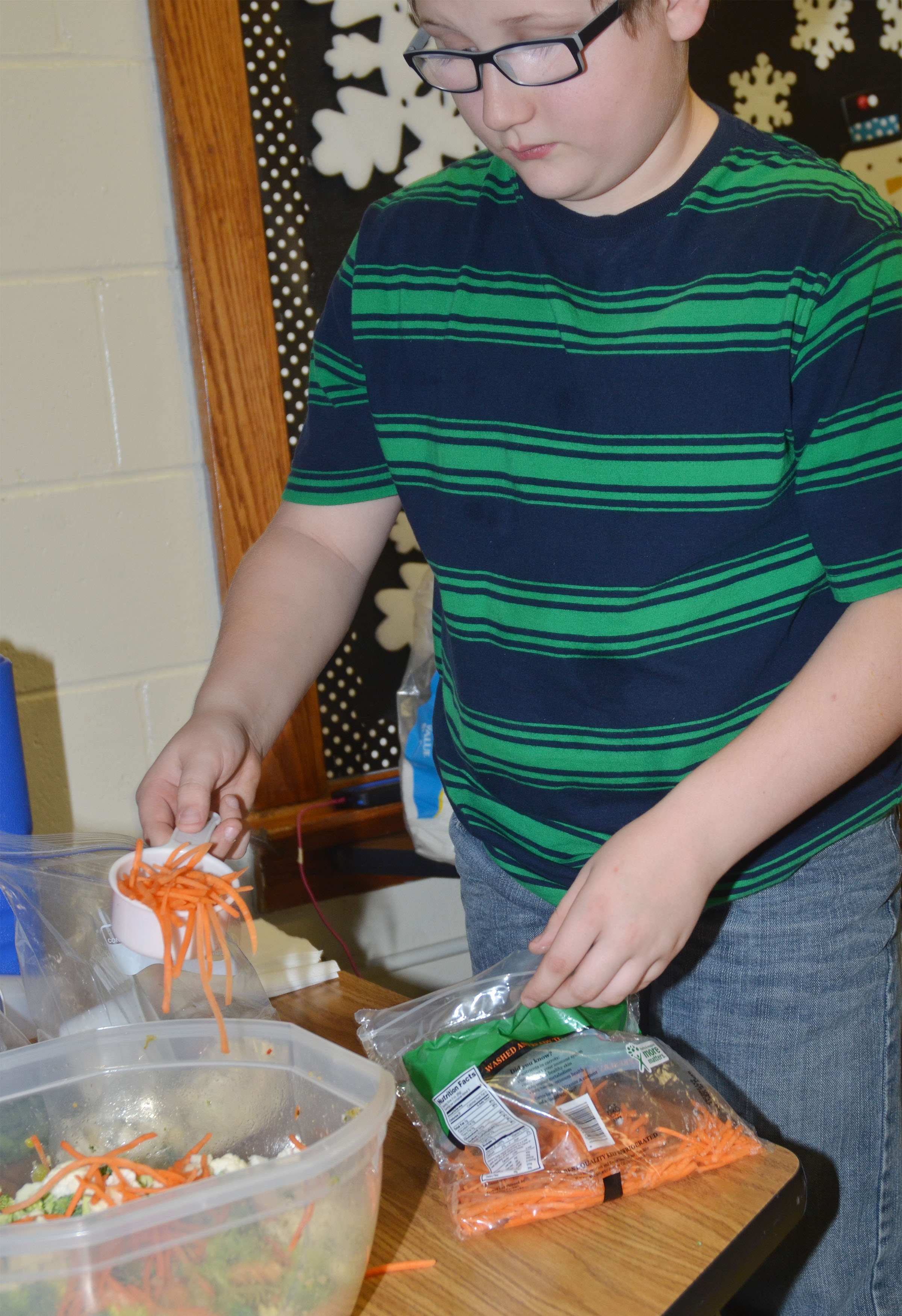 CMS fourth-grader Landon Rakes adds carrots to the class's pasta salad.