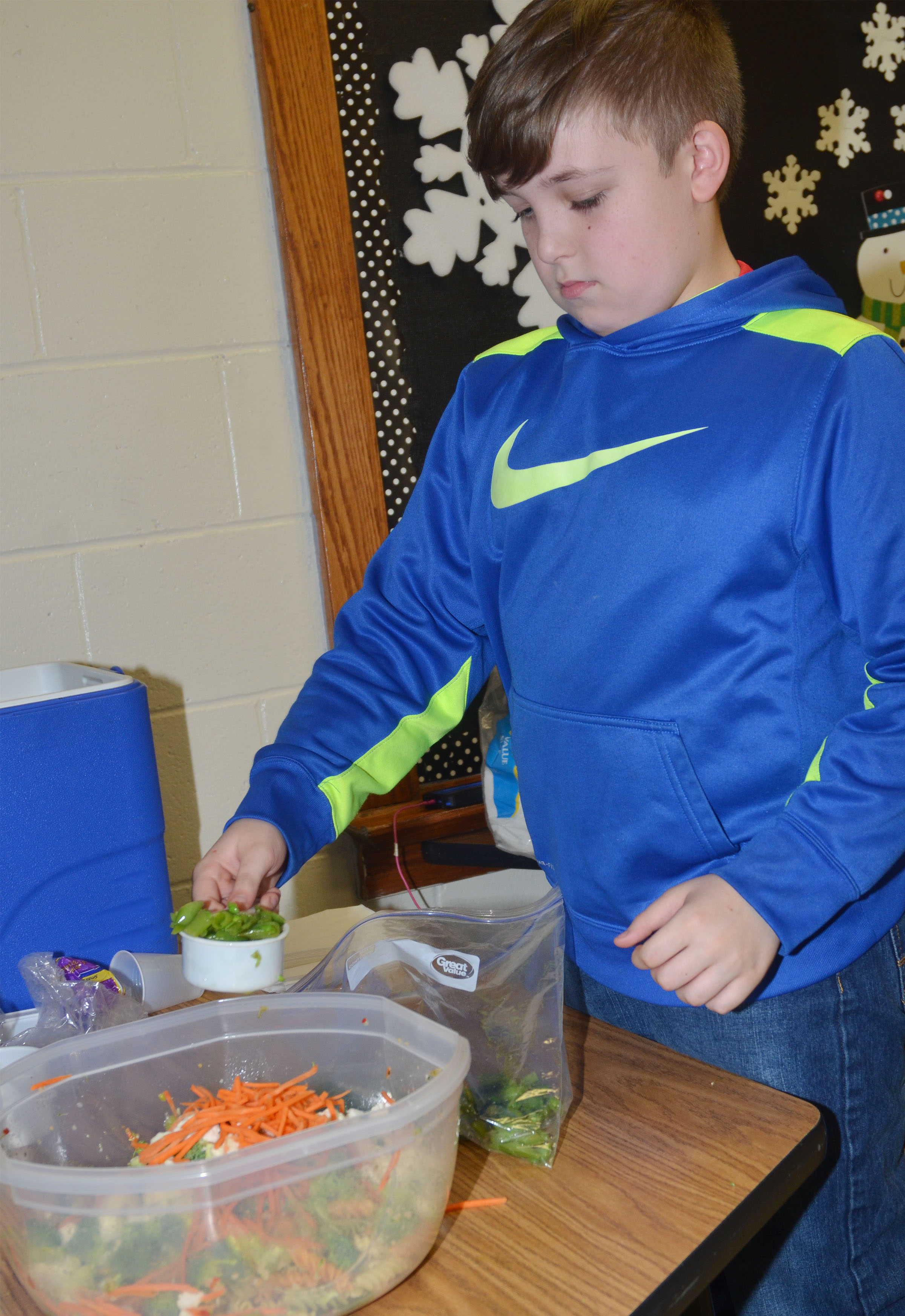CMS fourth-grader Skylar Wilhoite adds sugar snap peas to the class's pasta salad.