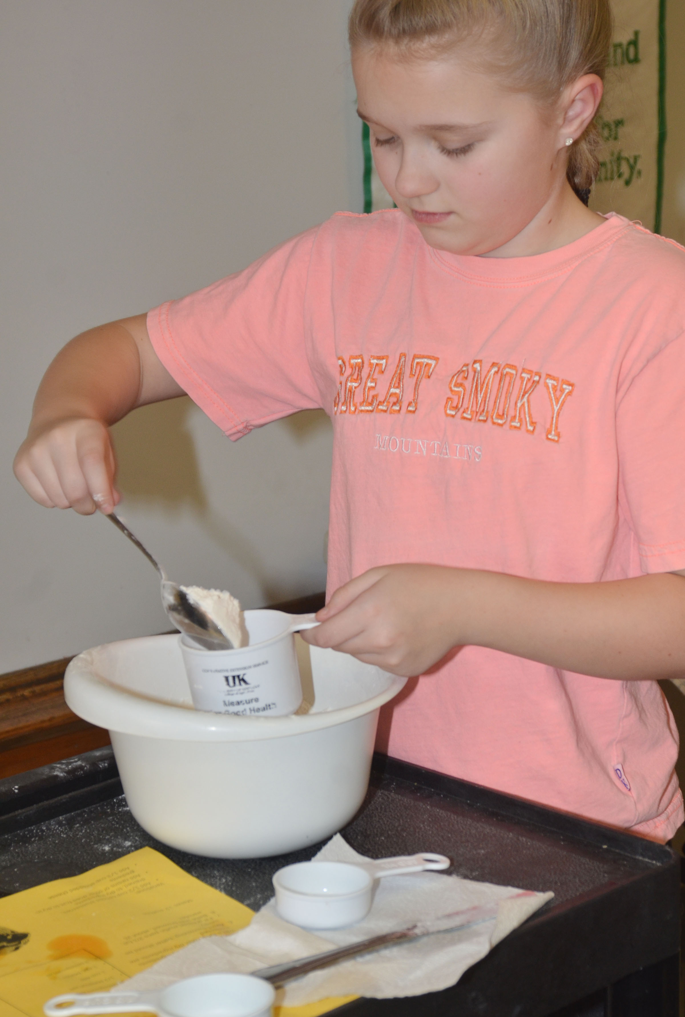CMS fifth-grader Lillee Byrne measures flour.