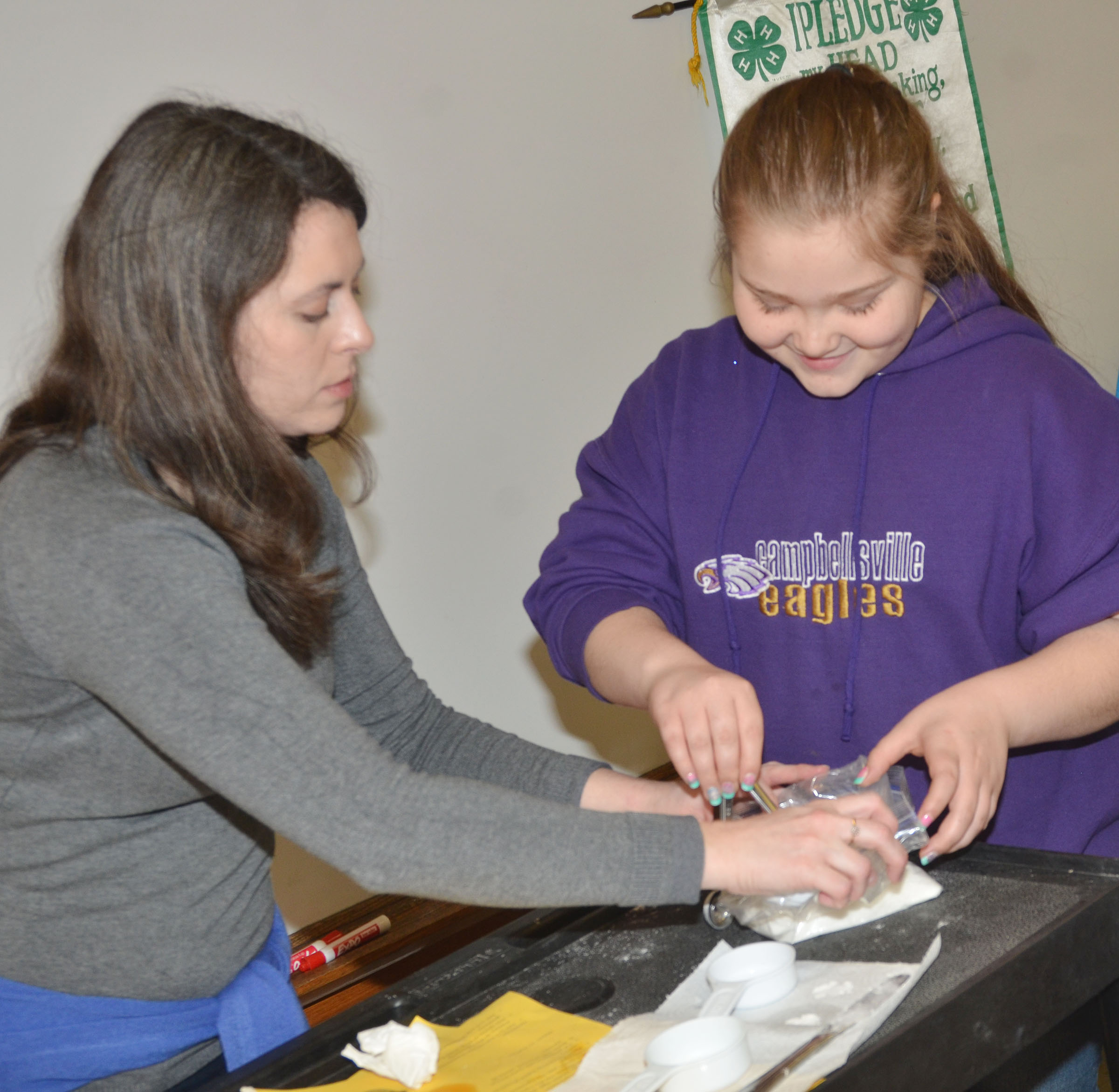 Taylor County Extension Agent for 4-H/Youth Development Amanda Sublett helps CMS fifth-grader Donna Schweickert measure sugar.