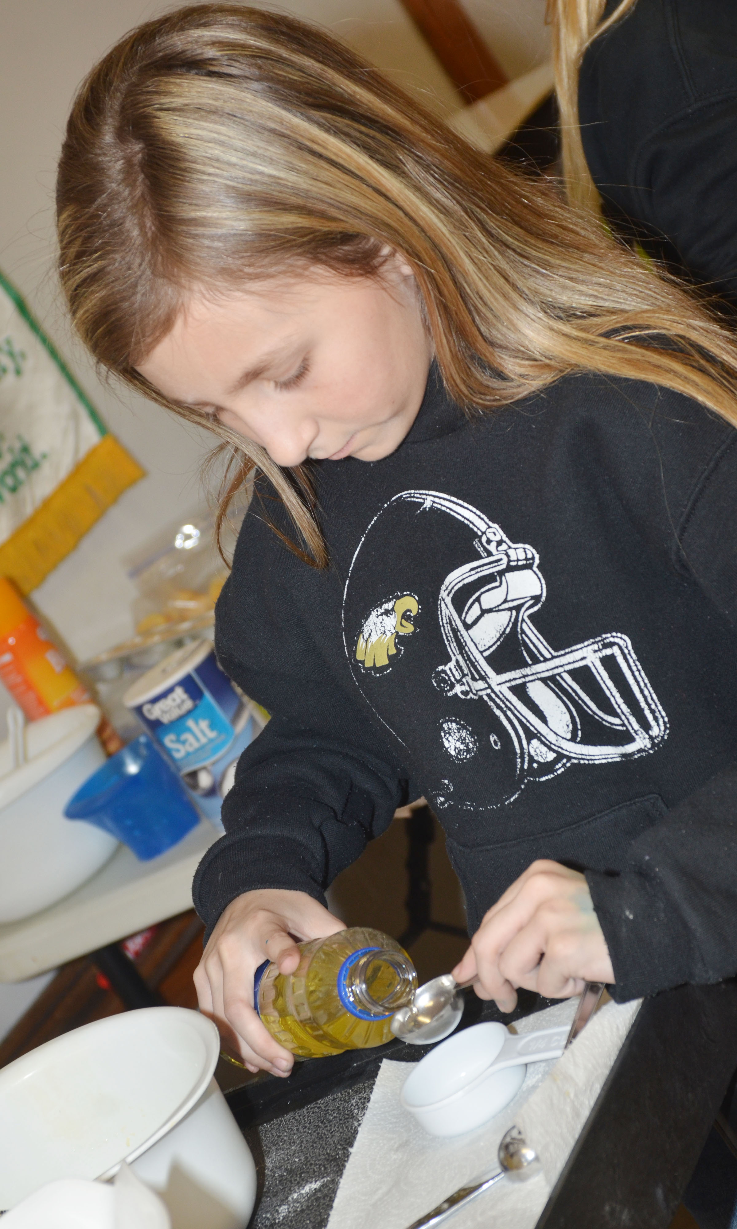 CMS fifth-grader Heather Leggett measures oil.