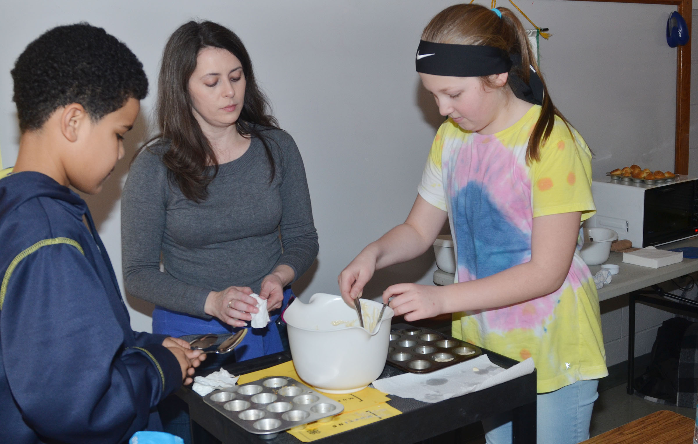 Taylor County Extension Agent for 4-H/Youth Development Amanda Sublett helps CMS fifth-graders Tashaun Hart, at left, and Ava Hughes scoop batter into muffin pans.