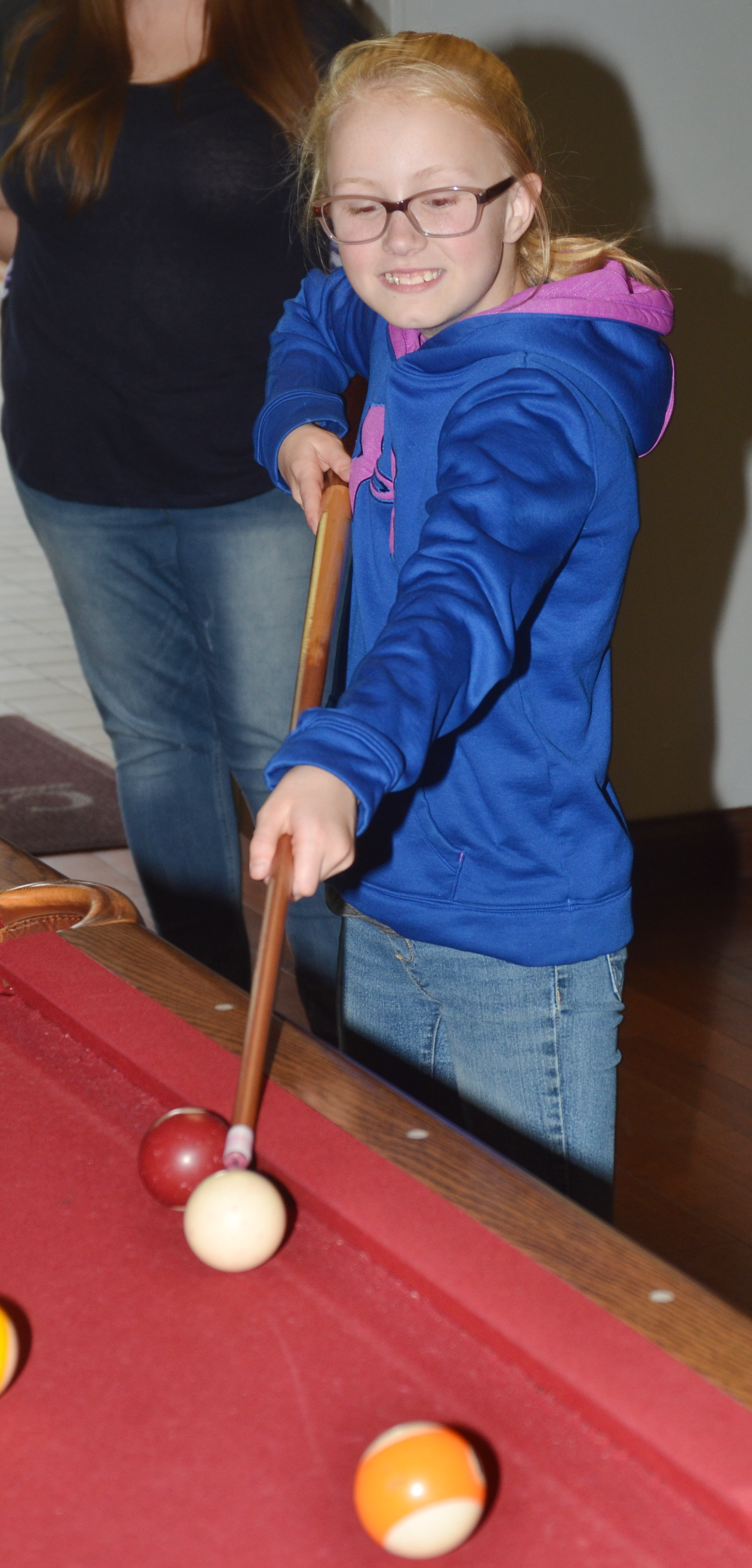 CMS fifth-grader Brianna Atwood plays pool at the Student Activities Center.